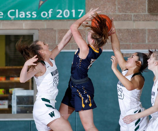 Williamston's Kenzie Lewis, left, and Jayda Bush, right, team up to block a shot by Haslett's Skyla Nosek, Friday, Jan. 11, 2019, in Williamston, Mich.