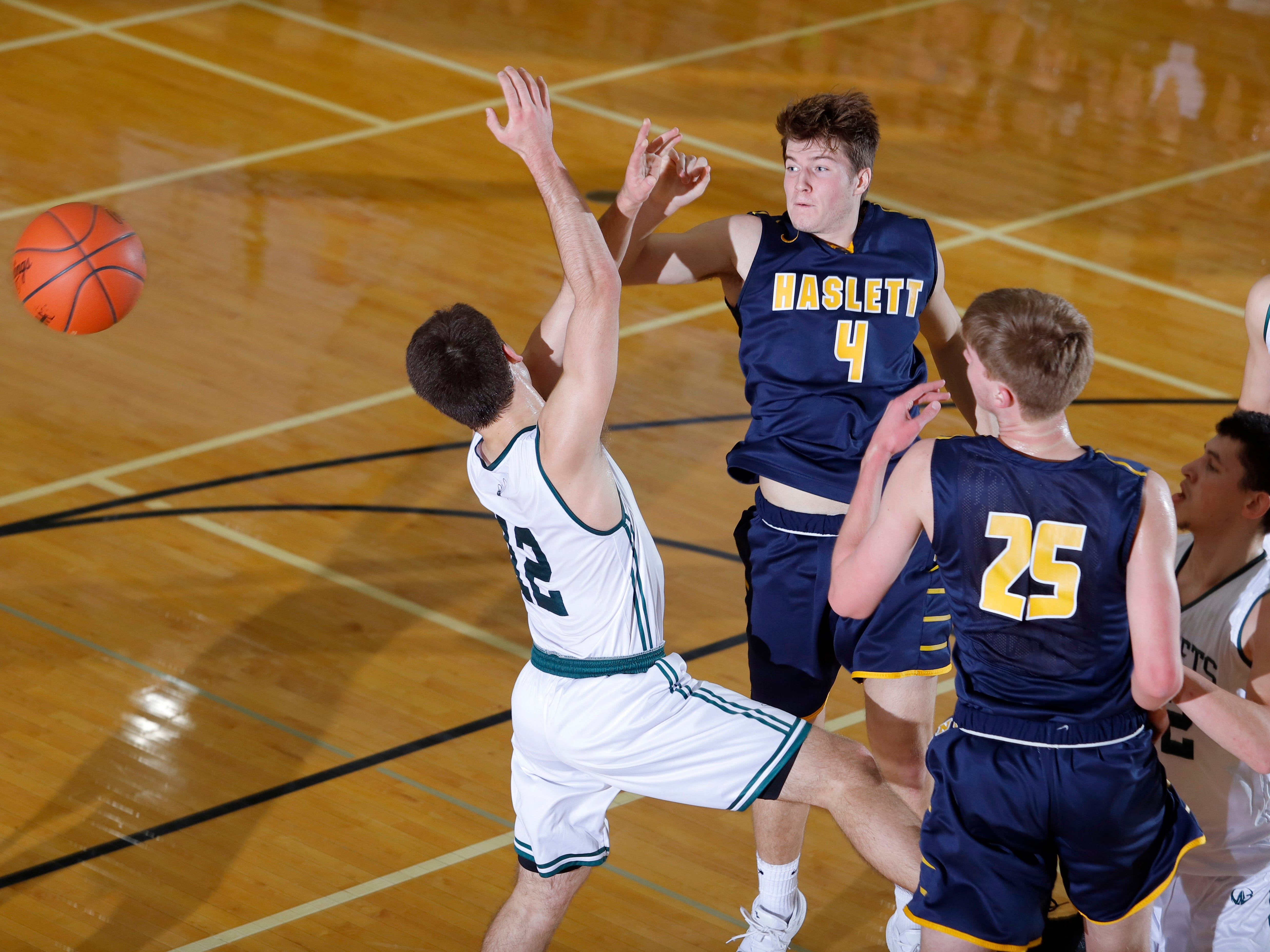 Williamston's Mitchell Cook, left, and Sean Cobb, right, and Haslett's Jaden Thelen (4) and Andrew Alchin (25) vie for a rebound, Friday, Jan. 11, 2019, in Williamston, Mich.