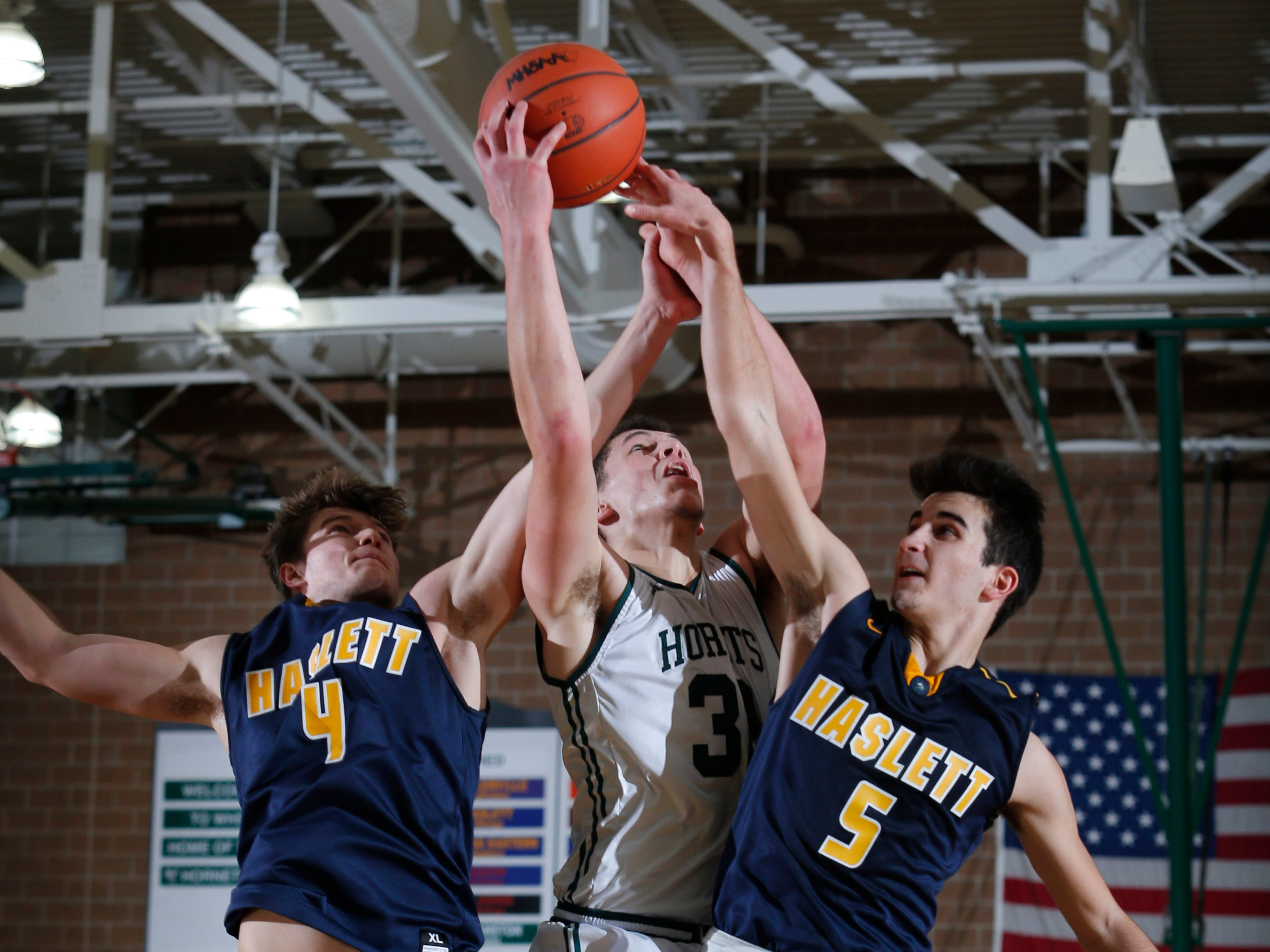 Williamston's Sean Cobb, center, and Haslett's Jaden Thelen, left, and Mitchell Mowid battle for a rebound, Friday, Jan. 11, 2019, in Williamston, Mich.