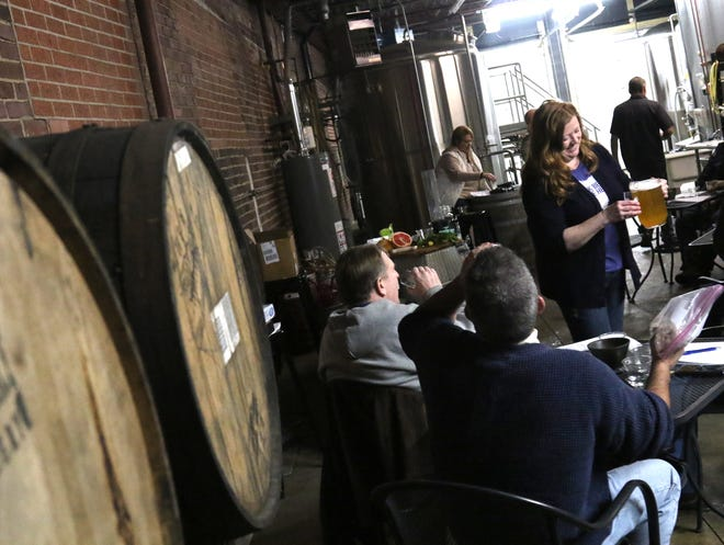 Phoenix Brewery's Carmone MacFarlane pours out samples during the Beer School session on Saturday. The topic of that day's class was the different infusions with Phoenix beers.
