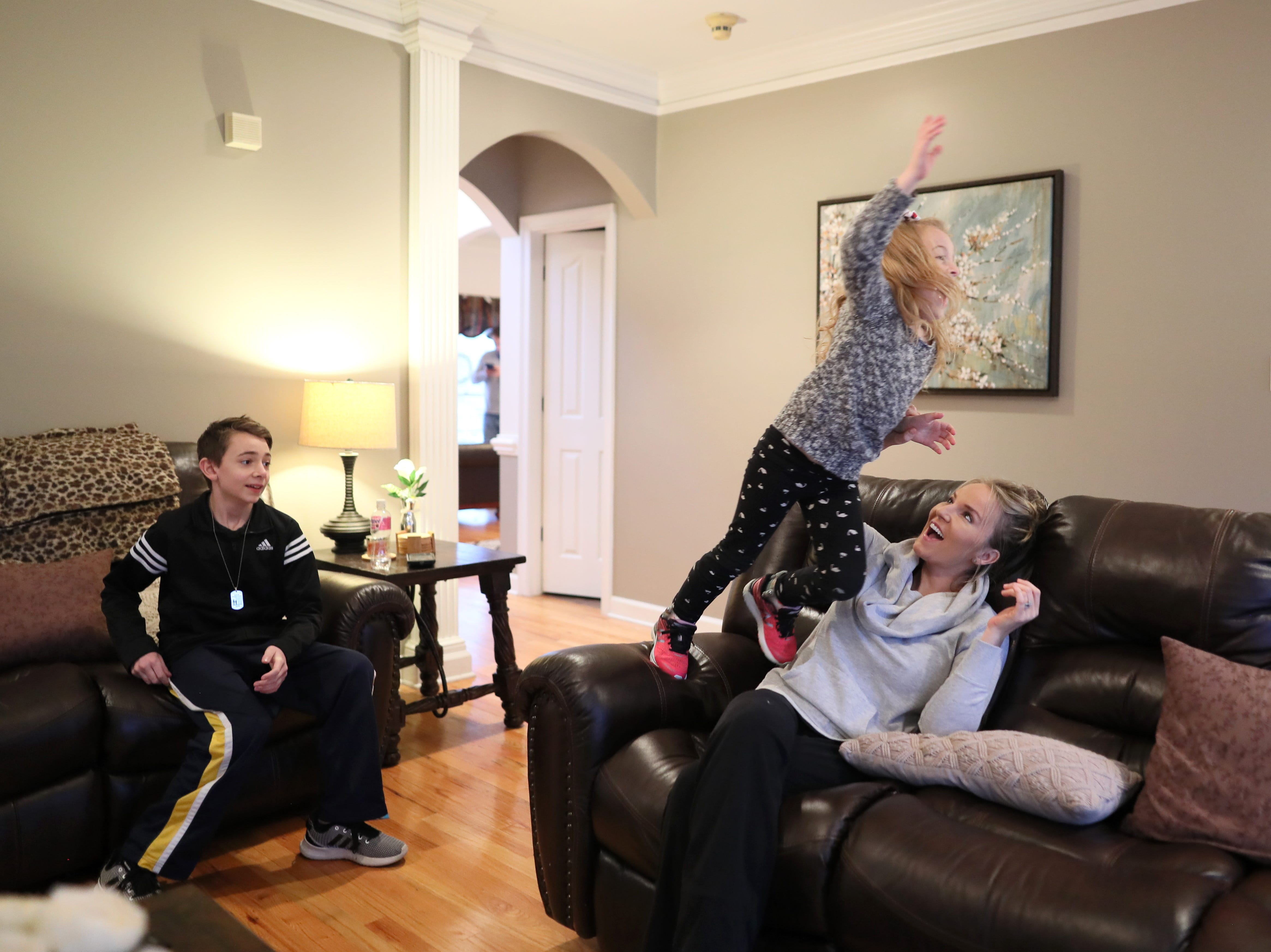 """Mom, watch me fly,"" says Ava, 6, to her mother Karon Reed as she leaps off the arm of the couch while her brother Aiden, 12, watches at the family home on Friday, Jan. 11, 2019. Though Ava lives with Charcot-Marie-Tooth Disease, she is an active 6-year-old with an adventuresome spirit."