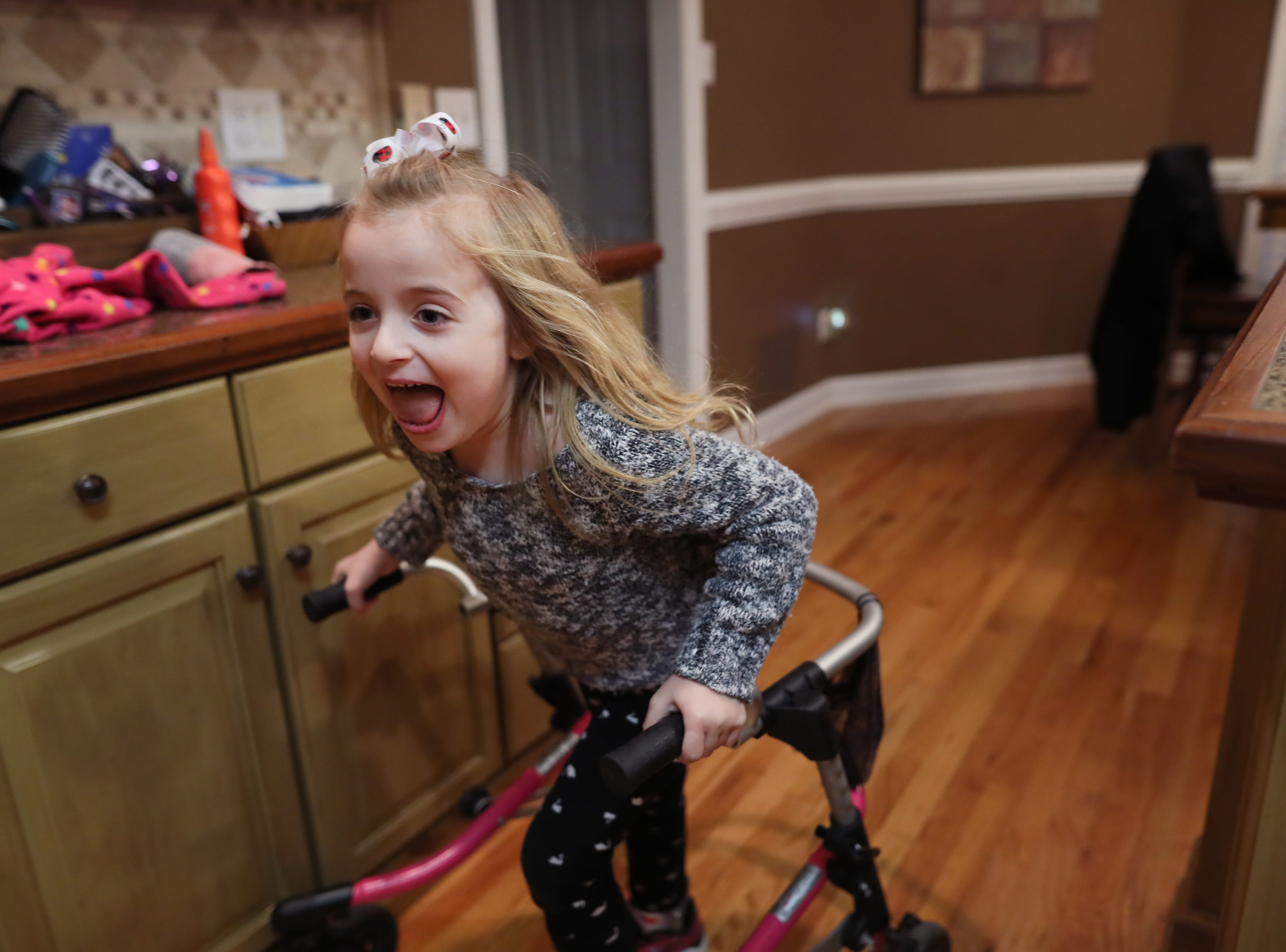 Ava Reed, 6, uses her walker to scramble around the family kitchen at their Arlington home on Friday, Jan. 11, 2019. Ava lives with Charcot-Marie-Tooth Disease, which affects peripheral nerves outside the brain that send signals to the body and can lead to weakened muscles and difficulty walking.