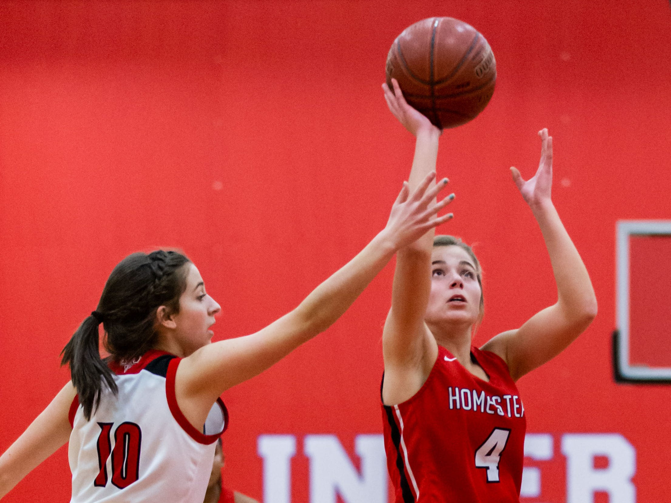 Homestead's Chloe Sileno (4) drives past Slinger's Maddie Rothenhoefer (10) for a layup during the game at Slinger on Friday, Jan. 11, 2019.