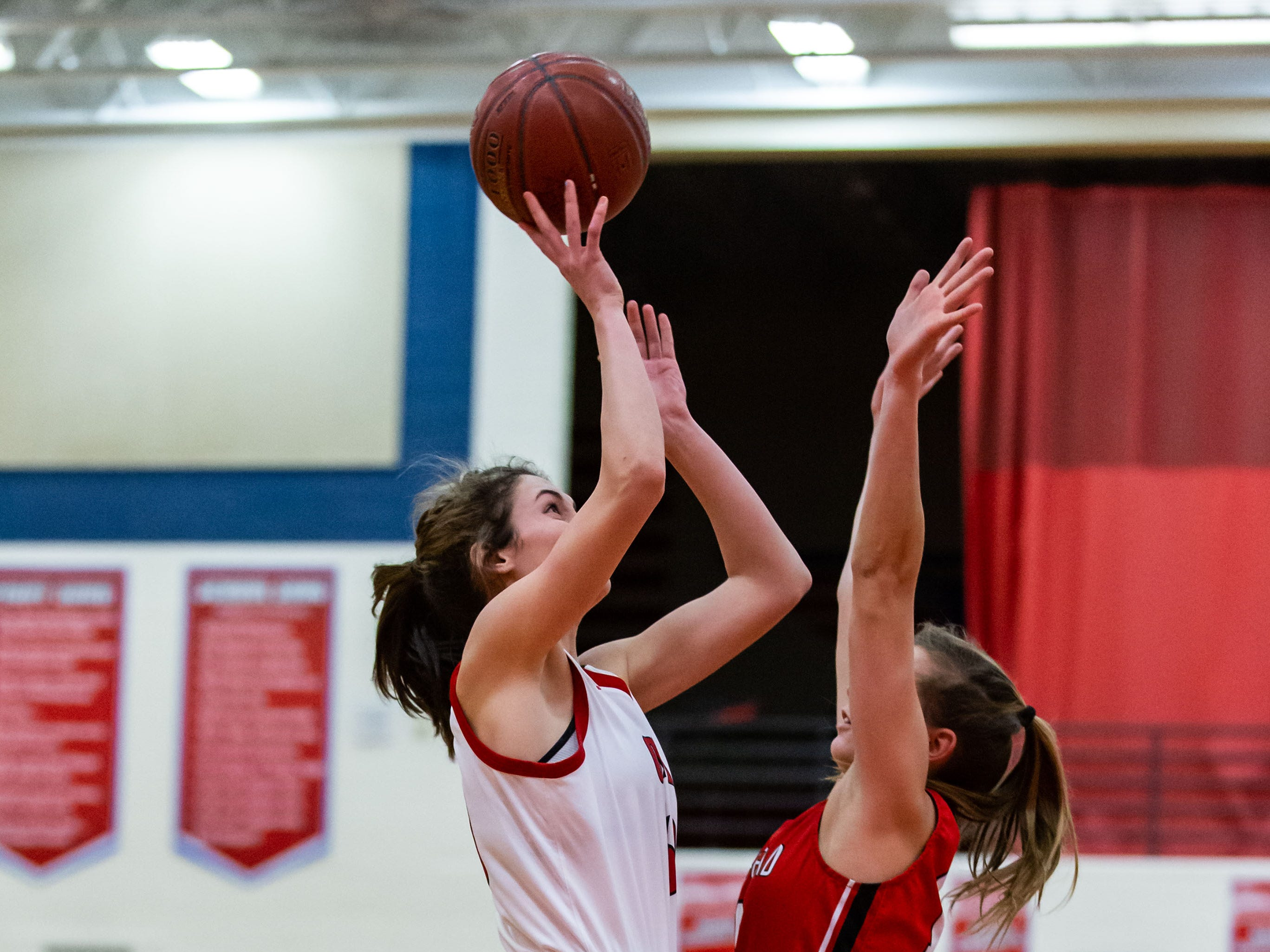 Slinger's Kacey Ott (left) elevates for a shot during the game at home against Homestead on Friday, Jan. 11, 2019.