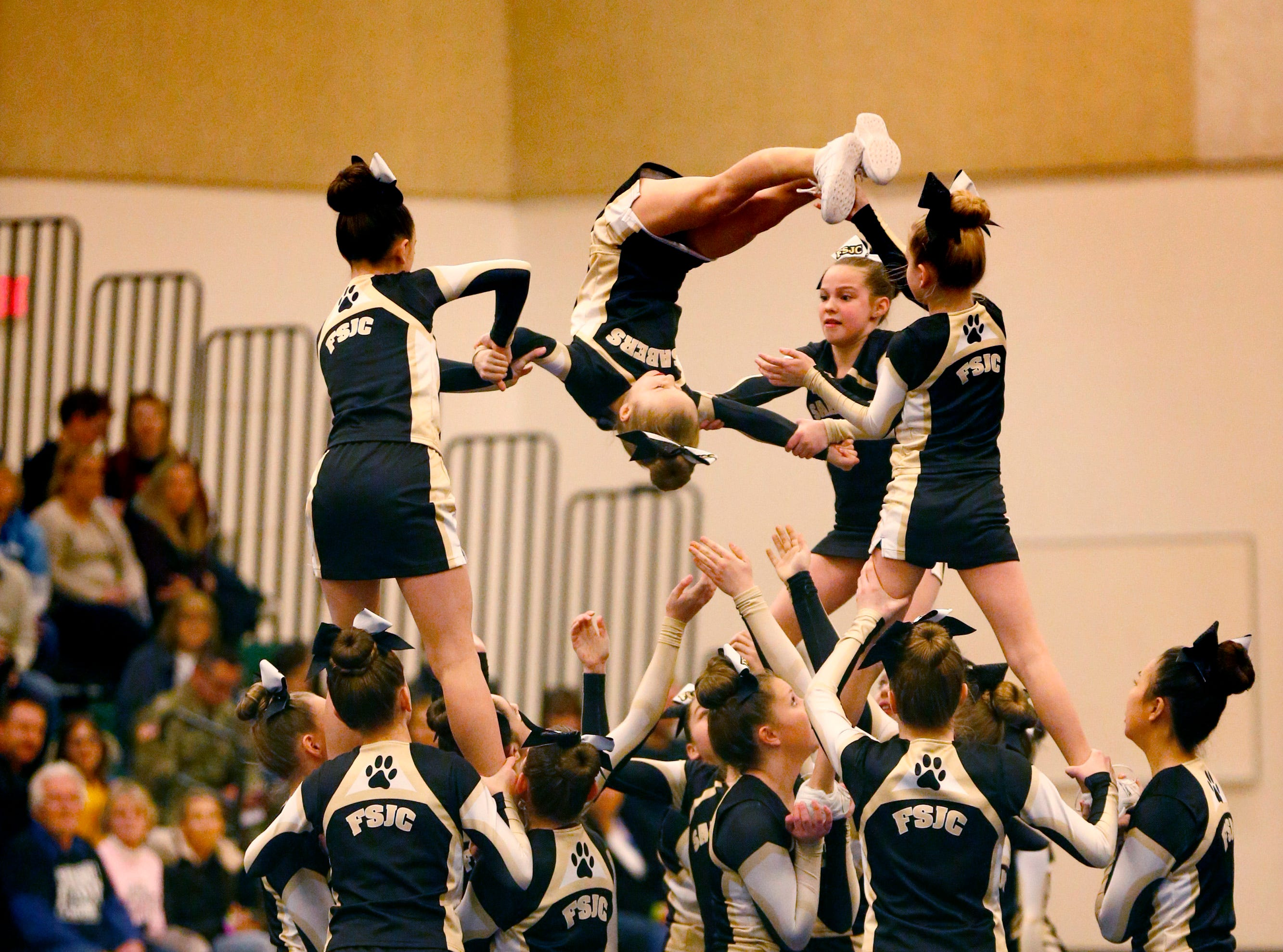 The Franklin Saber Jr. Cheer team flips out of a stack while competing in the middle school division during the Greenfield Xtreme Cheer competition at Greenfield High School on Jan. 12 that drew 56 teams competing in 13 divisions.