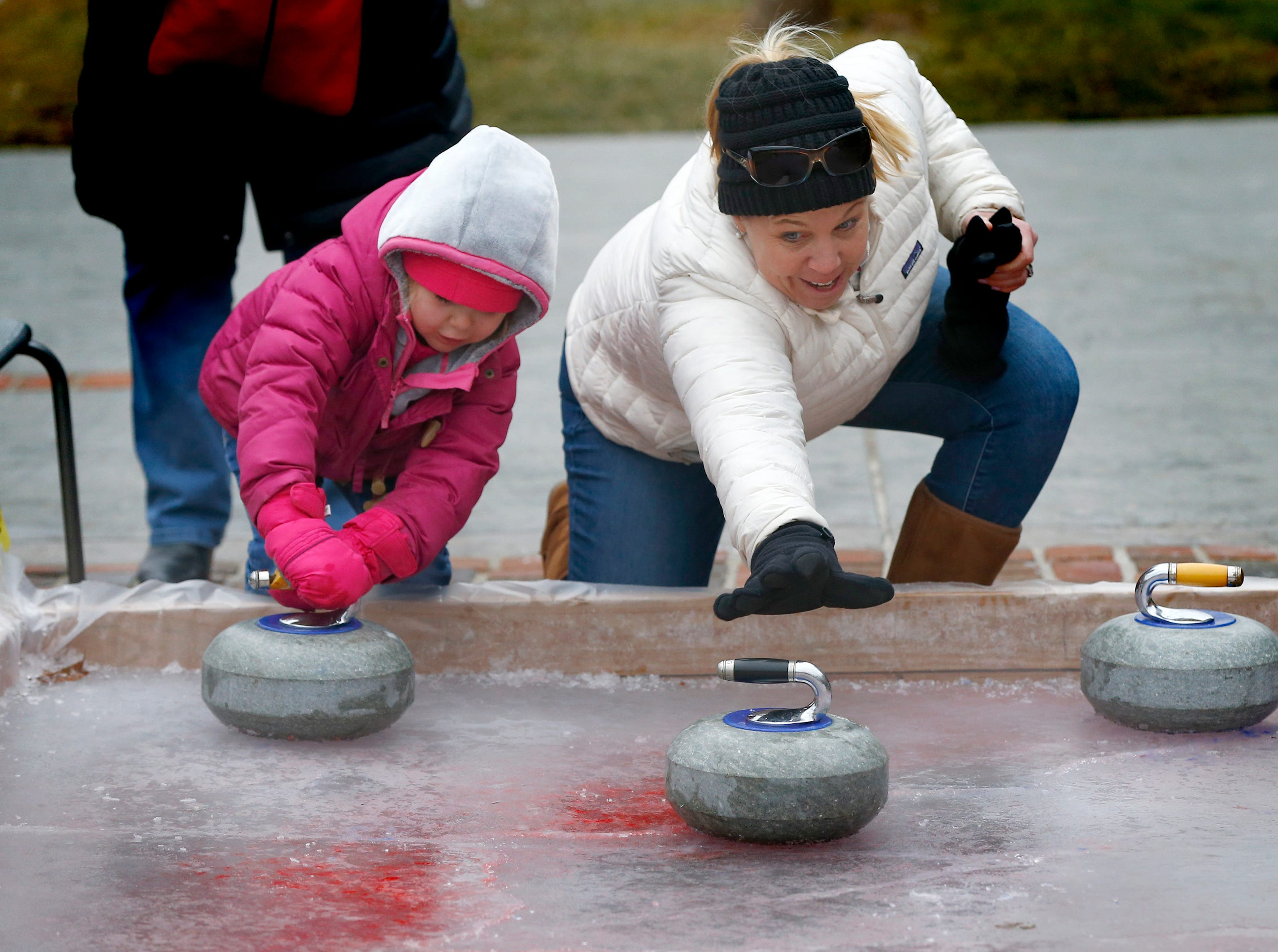 Abigail, 5, and Emlie Veinot try sliding stones on a curling rink run by the Kettle Moraine Curling Club in front of Revere's Tavern during the first DelaFreeze on Jan. 12. The event featured ice carvers and other activities throughout downtown Delafield.