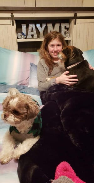 Jayme Closs smiles with the family pets at her aunt's home Saturday, two days after escaping from a cabin in Gordon in Douglas County. Authorities say Jayme  was kidnapped 88 days ago when her parents were murdered in her Barron home.