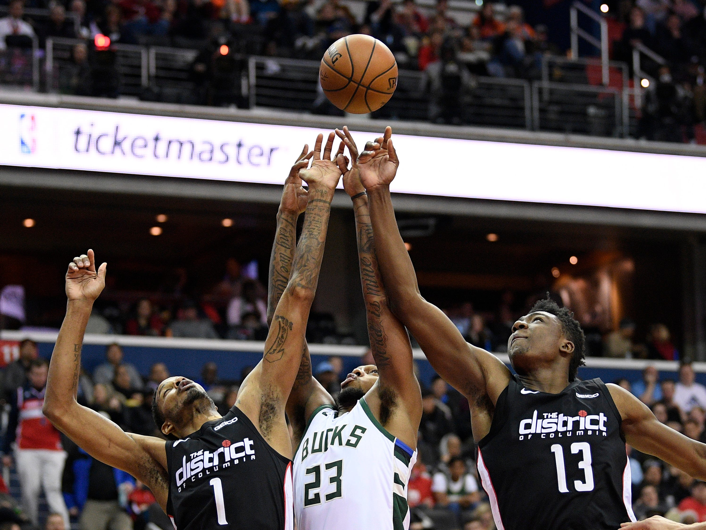 Sterling Brown of the Bucks battles for a rebound with Trevor Ariza (1) and Thomas Bryant of the Wizards on Friday night.