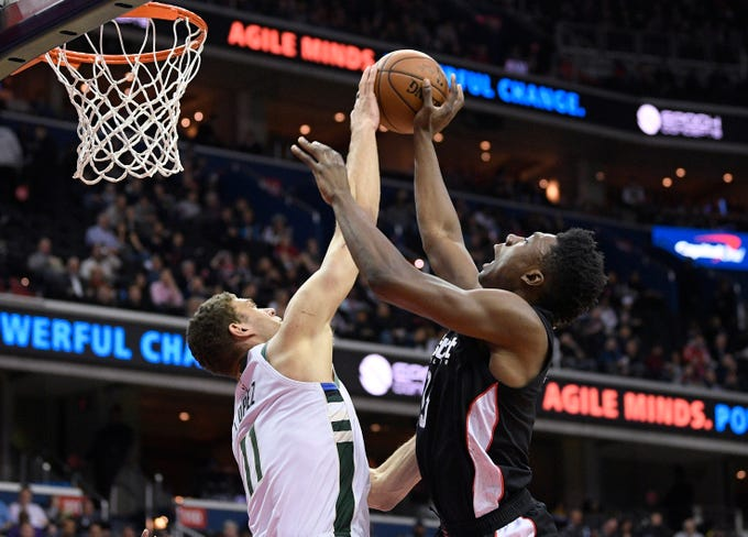 Bucks center Brook Lopez blocks a shot by Wizards center Thomas Bryant during the first half Friday in Washington, D.C.