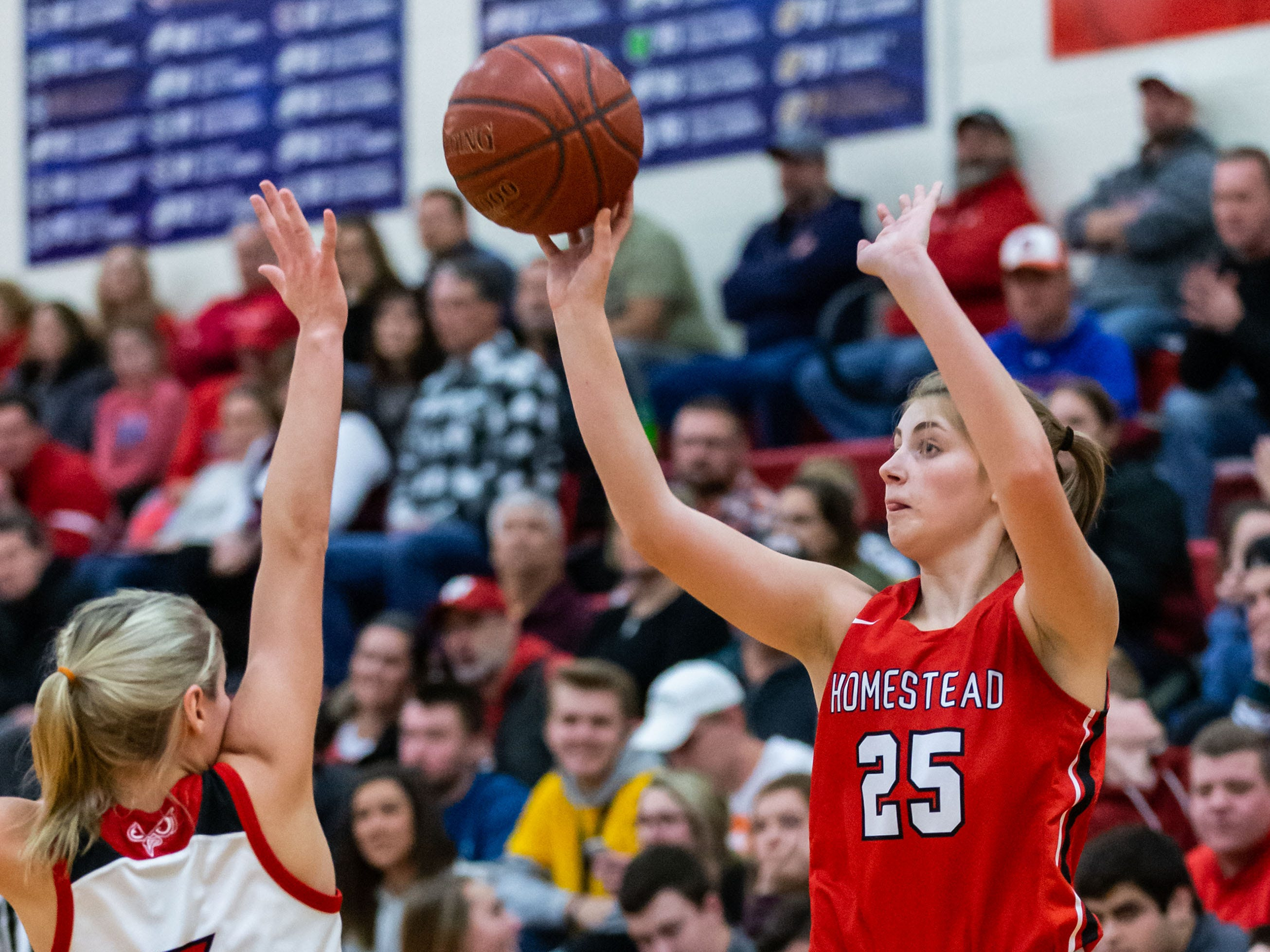 Homestead's Lexi Buzzell (25) elevates for a shot over Slinger's Sydney Reinhardt (5) during the game at Slinger on Friday, Jan. 11, 2019.