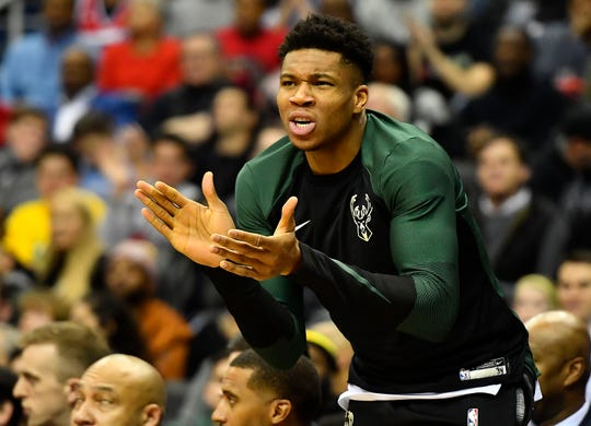 Giannis Antetokounmpo, who sat out the Bucks' game against the Wizards on Friday night with right quadriceps soreness and a left hip contusion, exhorts his teammates on from the bench.