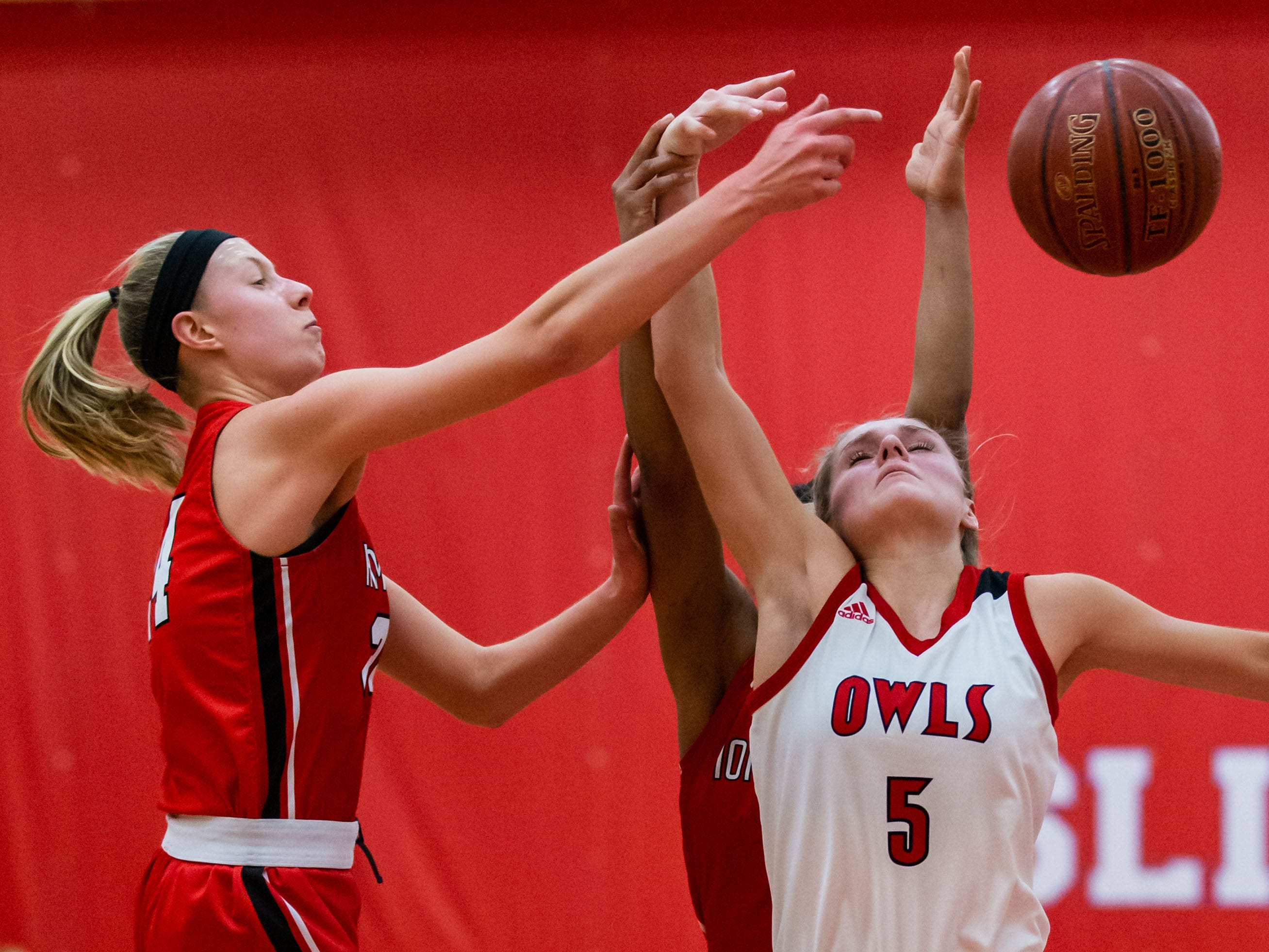 Homestead's Ally Rilling (left) battles for a rebound with Slinger's Sydney Reinhardt (5) and teammate Daja Young (obscured) during the game at Slinger on Friday, Jan. 11, 2019.