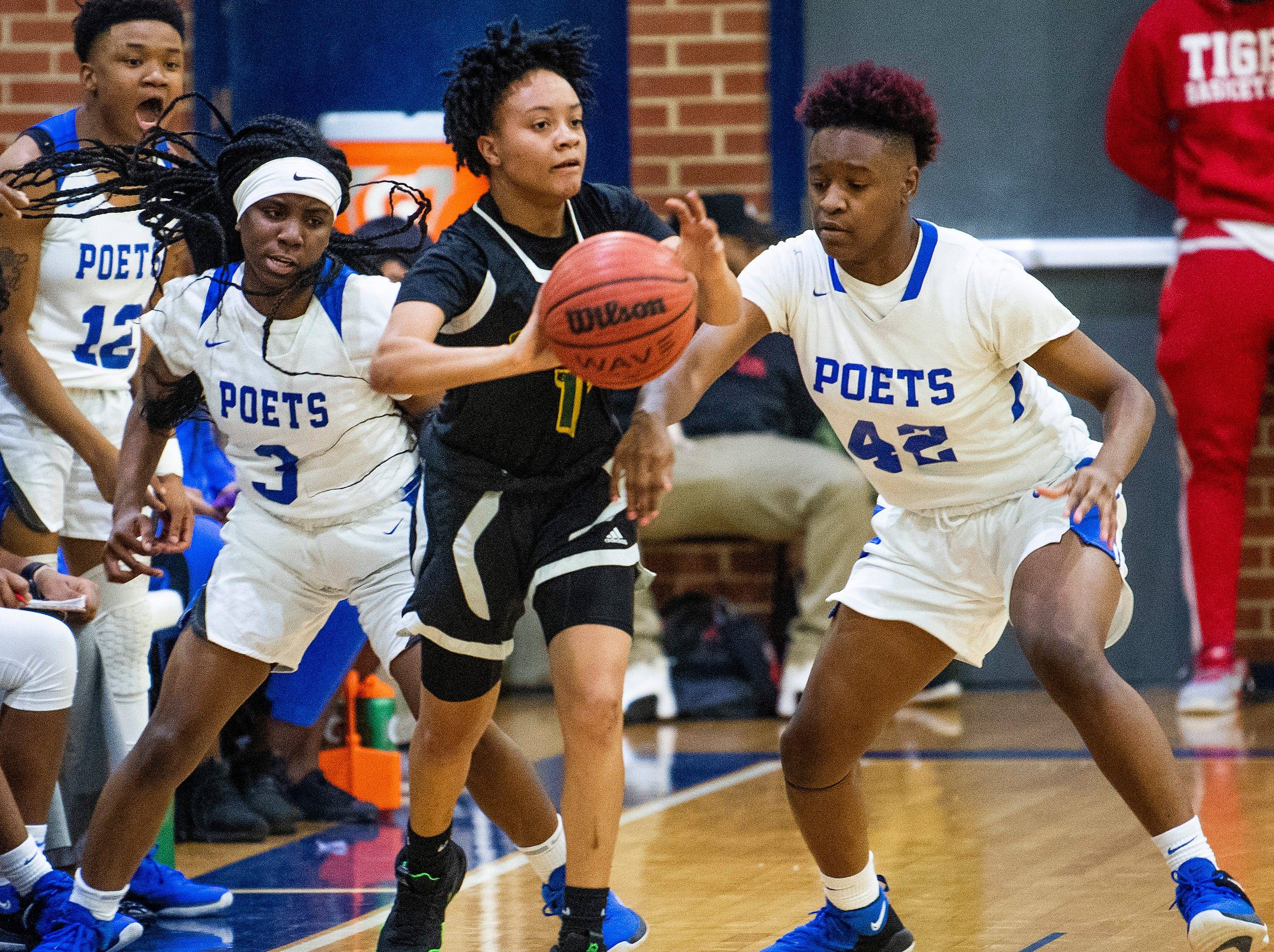Carver's Aaliyah Ellis (11) is double teamed by Lanier's Tamia Blair (3)  and Lanier's Nyana Reese (42) at the Lanier campus in Montgomery, Ala., on Friday January 11, 2019.