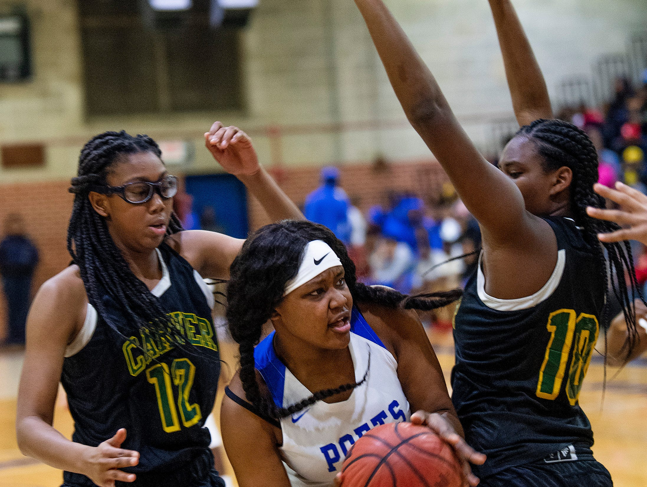 Lanier's Kadresha Smith (33) is defended by Carver's Mya Barnes (12)  and Carver's Bre anna Rhodes (10) at the Lanier campus in Montgomery, Ala., on Friday January 11, 2019.
