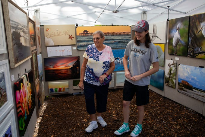 "Susan Stec, left, and her granddaughter Kaylee Stec look over the photography by Jane ""Dr. Jane"" Ruprecht during the Naples Artcrafters' monthly art show, Saturday, Jan. 12, 2019, in Cambier Park in Naples."