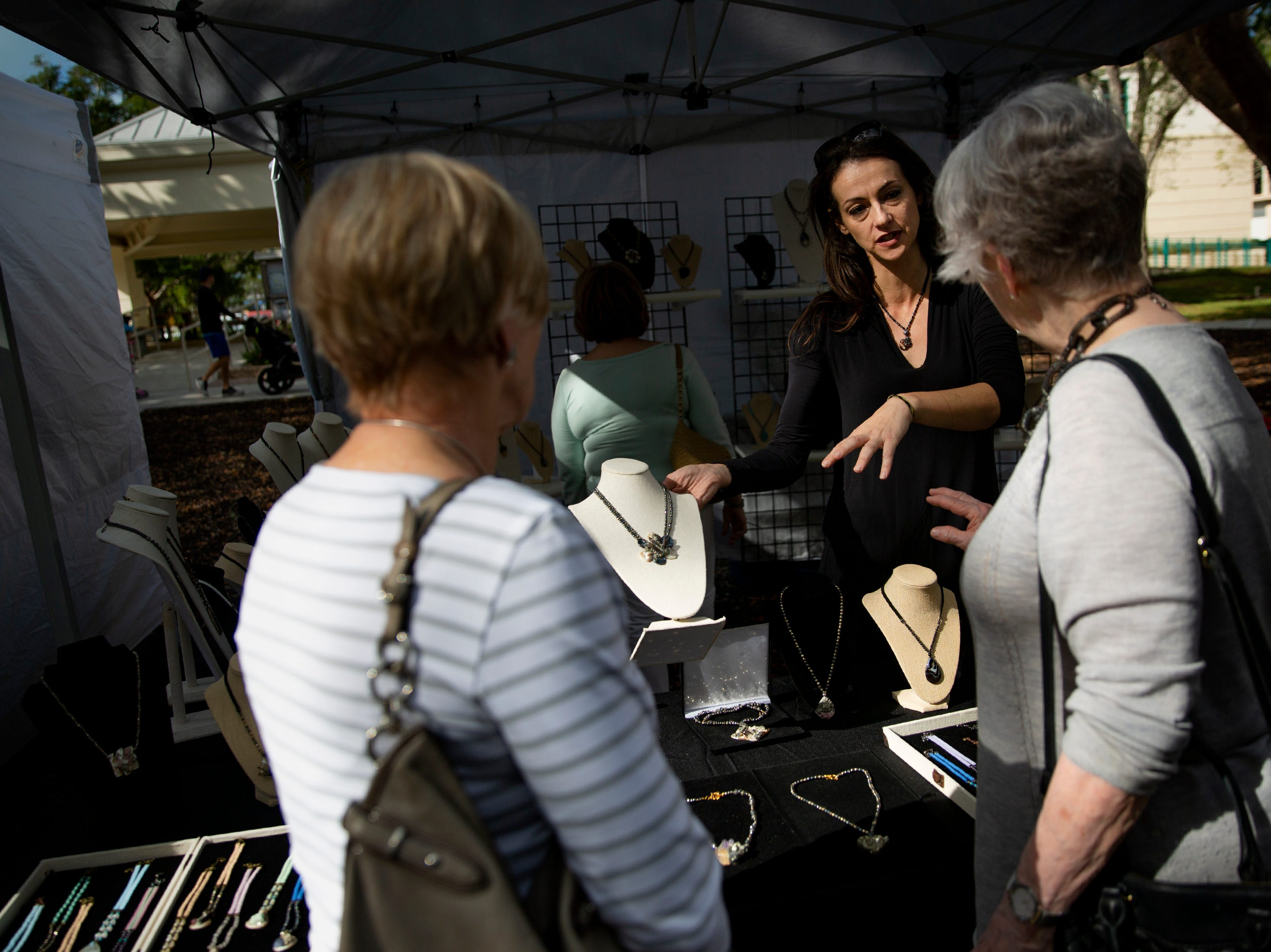 Jewelry designer Gordana Jordanoska, owner of Zagat Jewelry, talks about her work to visitors at the Naples Artcrafters' monthly art show, Saturday, Jan. 12, 2019, in Cambier Park in Naples.