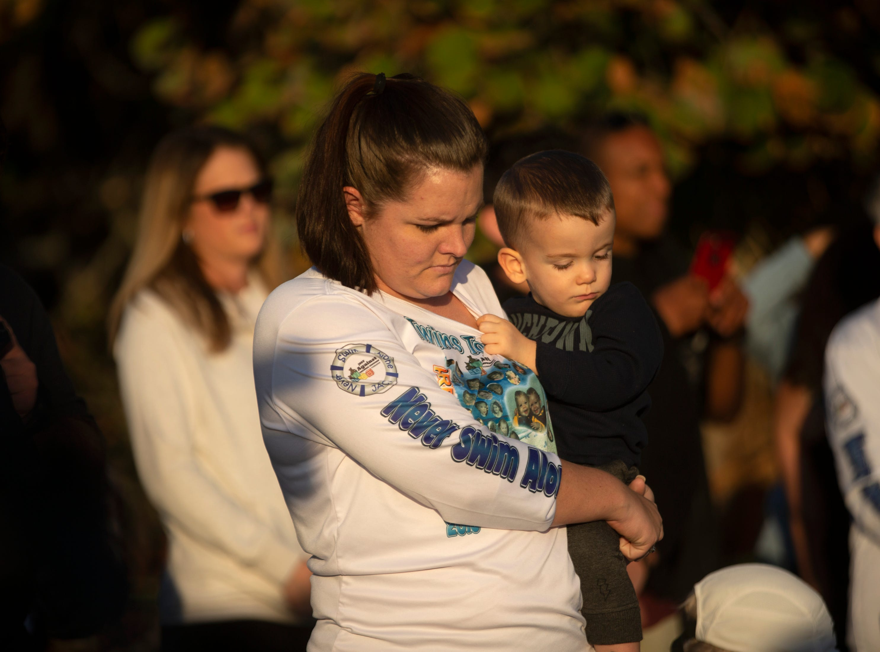 Jessica Jamieson and her son Liam DeMello bow their heads to remember the 48 local children who died due to drowning during the 6th Annual Twin Tot Walk Vigil, Friday, Jan. 11, 2019, at Vanderbilt Beach.