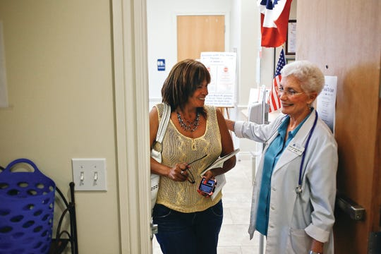 Neighborhood Health Clinic founder Nancy Lascheid, right, welcomes Debra Knight as she enters the clinic in Naples on Thursday Sept. 12, 2013.
