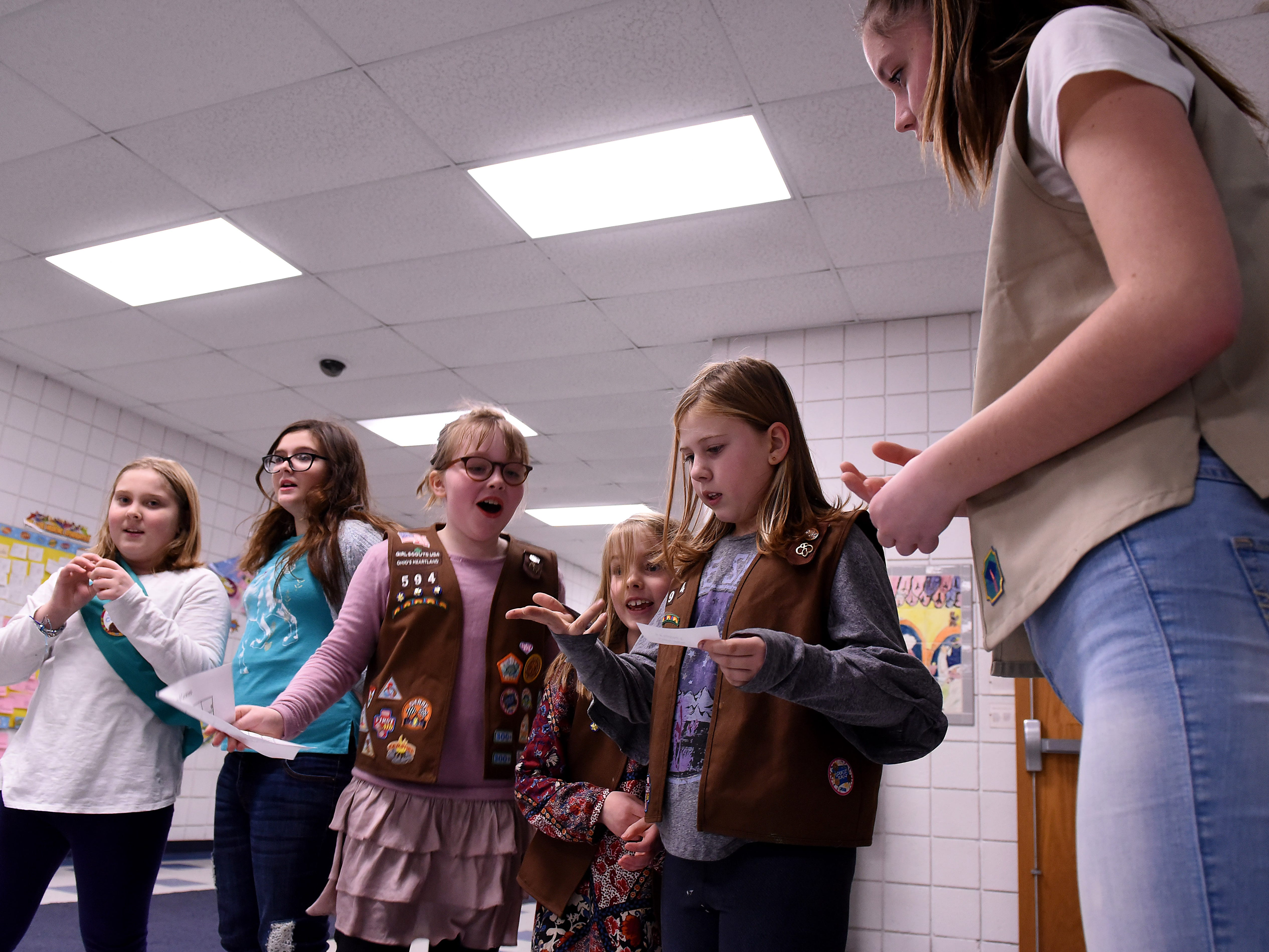 Junior Girl Scouts Elizabeth Lammbert and Scarlett Woltz compete against Brownies Ande Potaracke, Lola Phennicie, and Charlie Cholewa in a cookie cost math game as Ambassador Scout Maggie Reinhardt checks their math during a cookie rally at Granville Elementary on Friday, Jan. 11, 2019. Scouts meet to sample cookies, practice making change and calculating cost, and other entrepreneur skills during the event to start the Girl Scout cookie season. Local scouts will be taking orders through January 27th and then will be selling at booths locally through March 24.