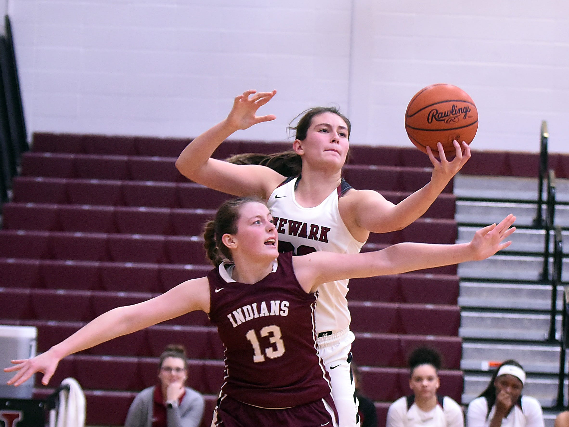 Canal Winchester junior Natalie Rarick and Newark sophomore Abby Derwacter fight for a rebound during the second half of Friday night's game at Newark High School. The Wildcats won 70-49.