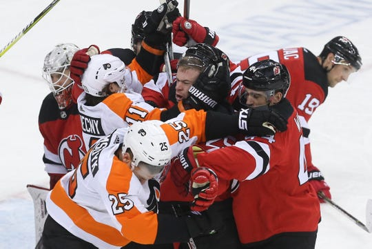 Jan 12, 2019; Newark, NJ, USA; The New Jersey Devils and the Philadelphia Flyers fight during the third period at Prudential Center.
