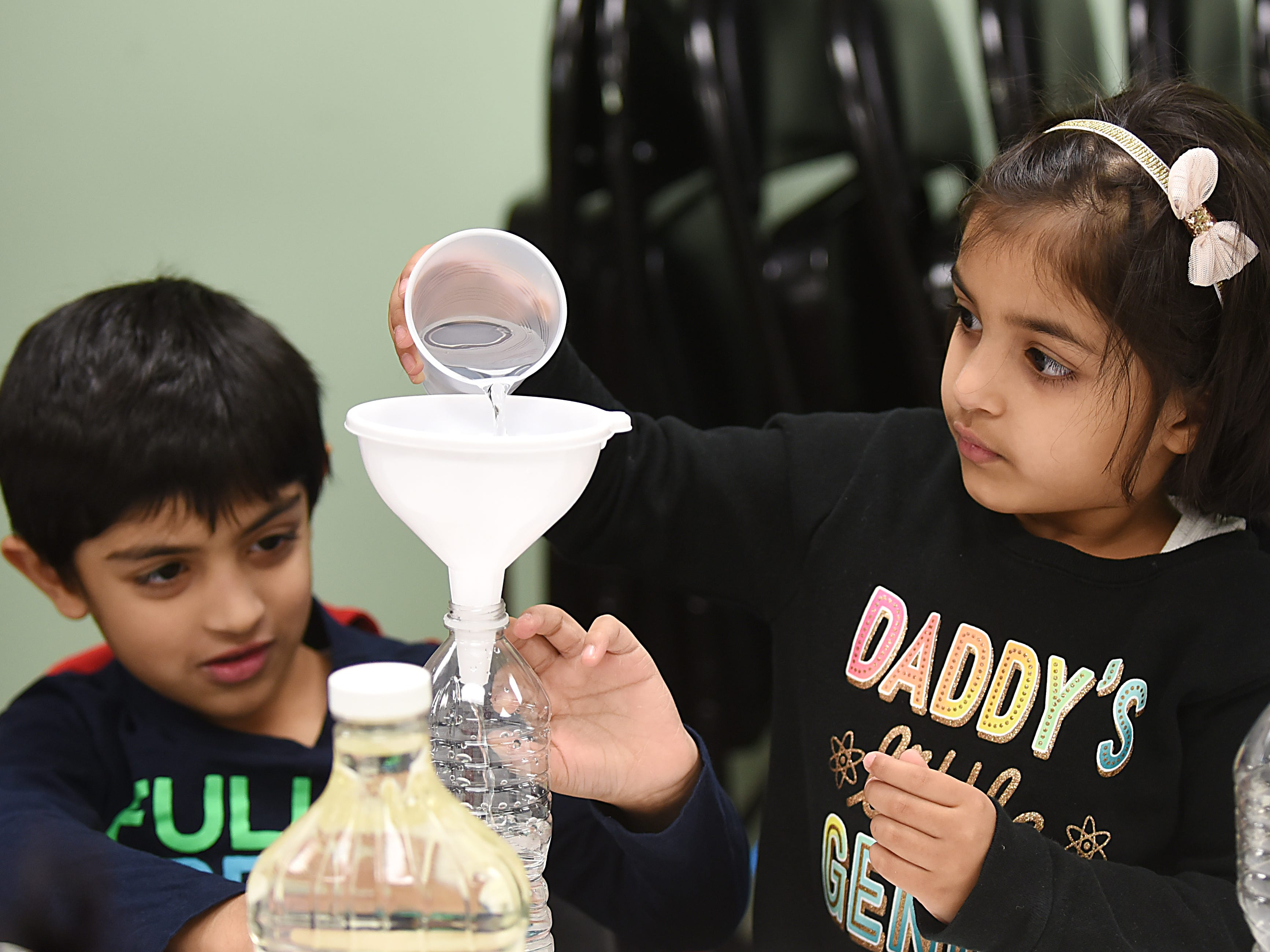 Children make a snowstorm in a bottle as part of the STEM Saturday series at East Rutherford Memorial Library on Saturday January 12, 2019. Rayoyau Jaweid, 5 and Areebah Jaweid, 4 pour water into a bottle.