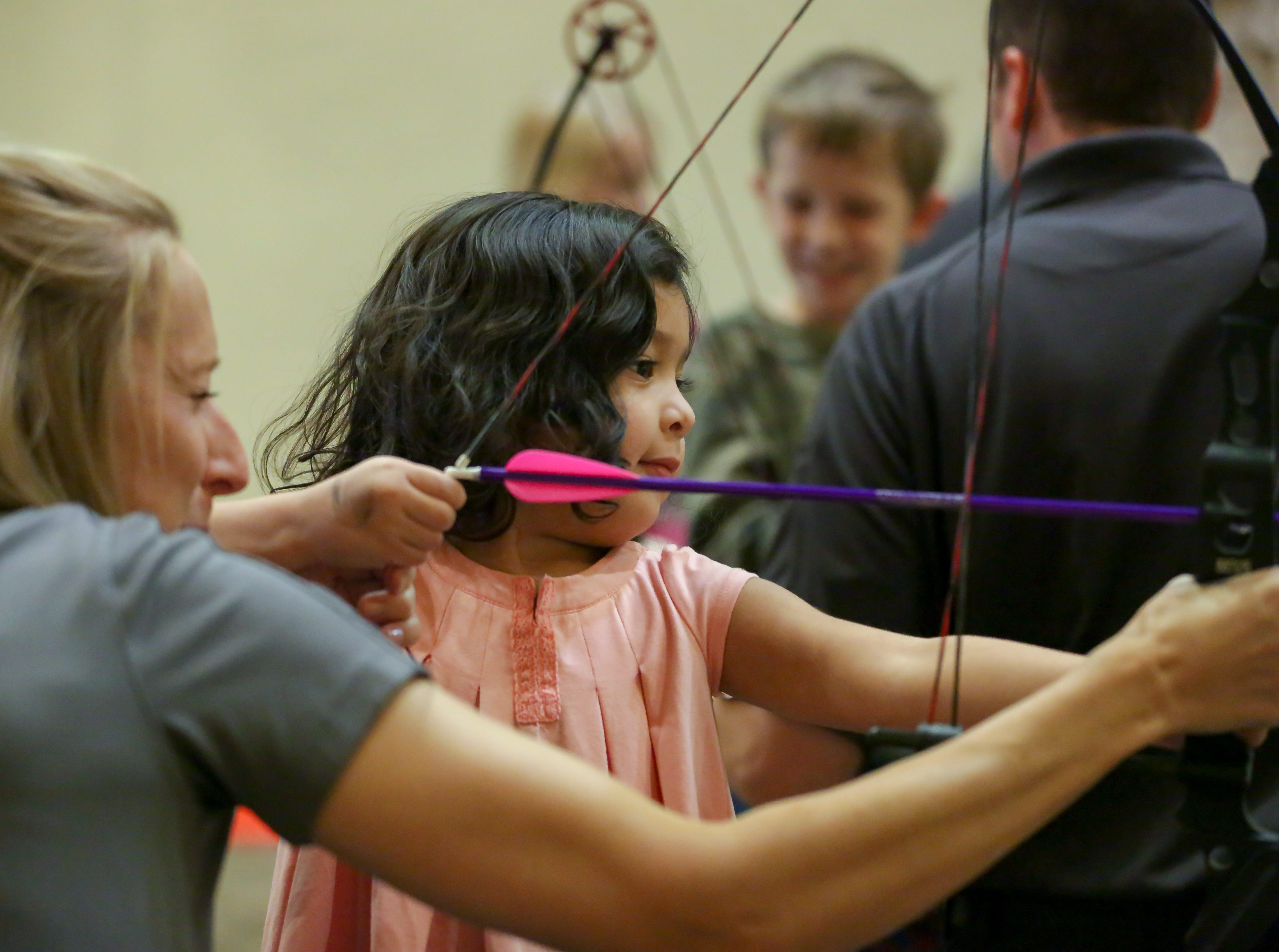 Aleena Gonzales, 3, of Las Cruces, learns how to use a Mathews Genesis bow on Saturday, Jan. 12, 2019, during the 2019 Mesilla Valley Outdoor Expo at the Las Cruces Convention Center. Assisting Gonzales is New Mexico Department of Game & Fish communications director Tristanna Brickford.