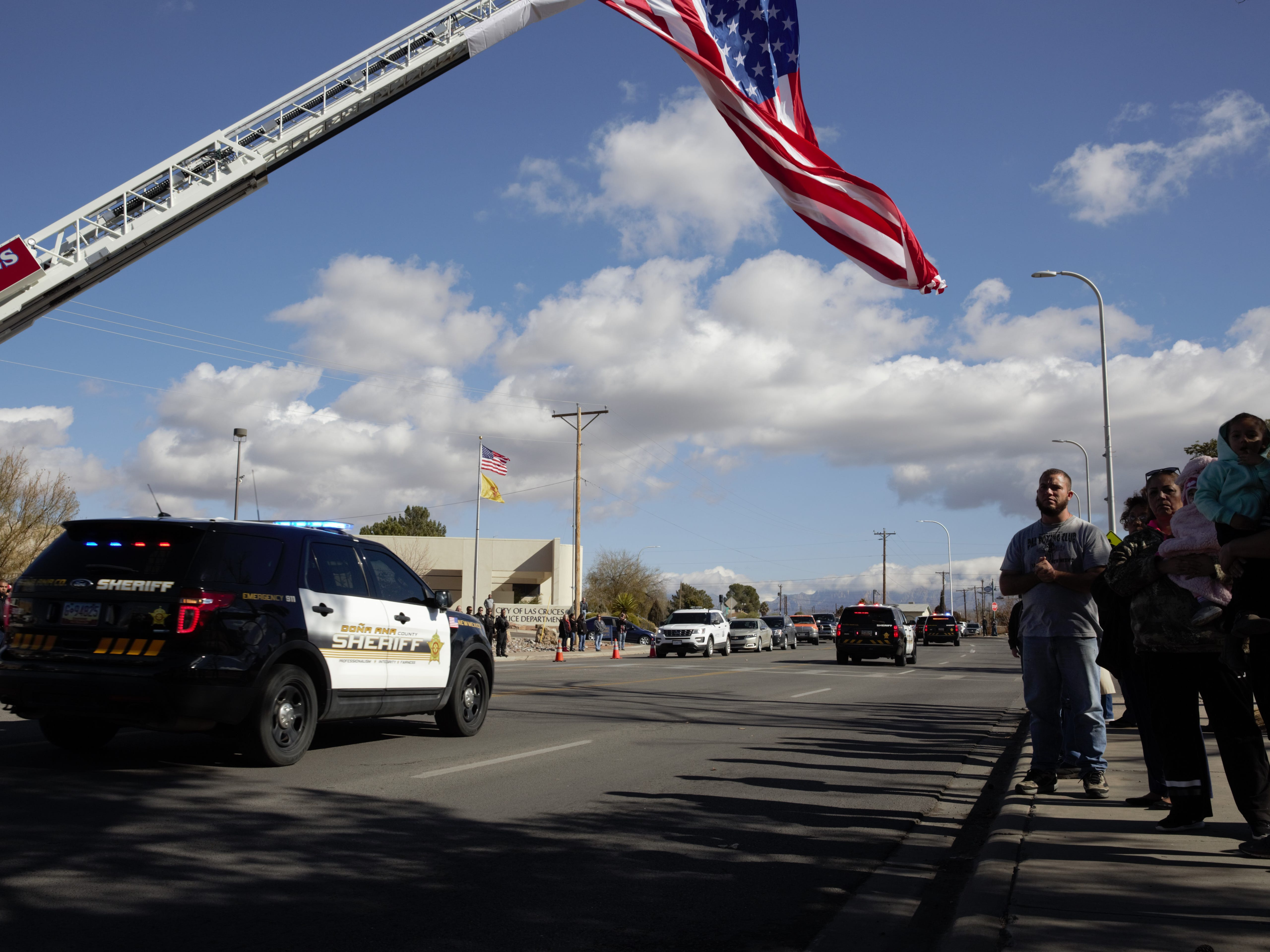 Personnel from a number of area law enforcement agencies, including the county sheriff's department, process east on Picacho Avenue underneath a giant flag hung to honor retired Las Cruces Police Department Chief Jaime Montoya, who died recently from cancer. The funeral and procession took place Friday, Jan. 11, 2019.