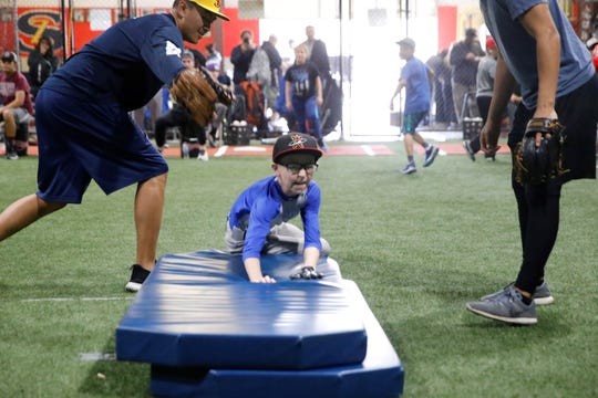 Wesley Kennedy of Farmington beats the throw to the bag during base running drills at the fourth annual Grinders for Grace baseball camp Saturday at the Strike Zone training facility in Farmington.