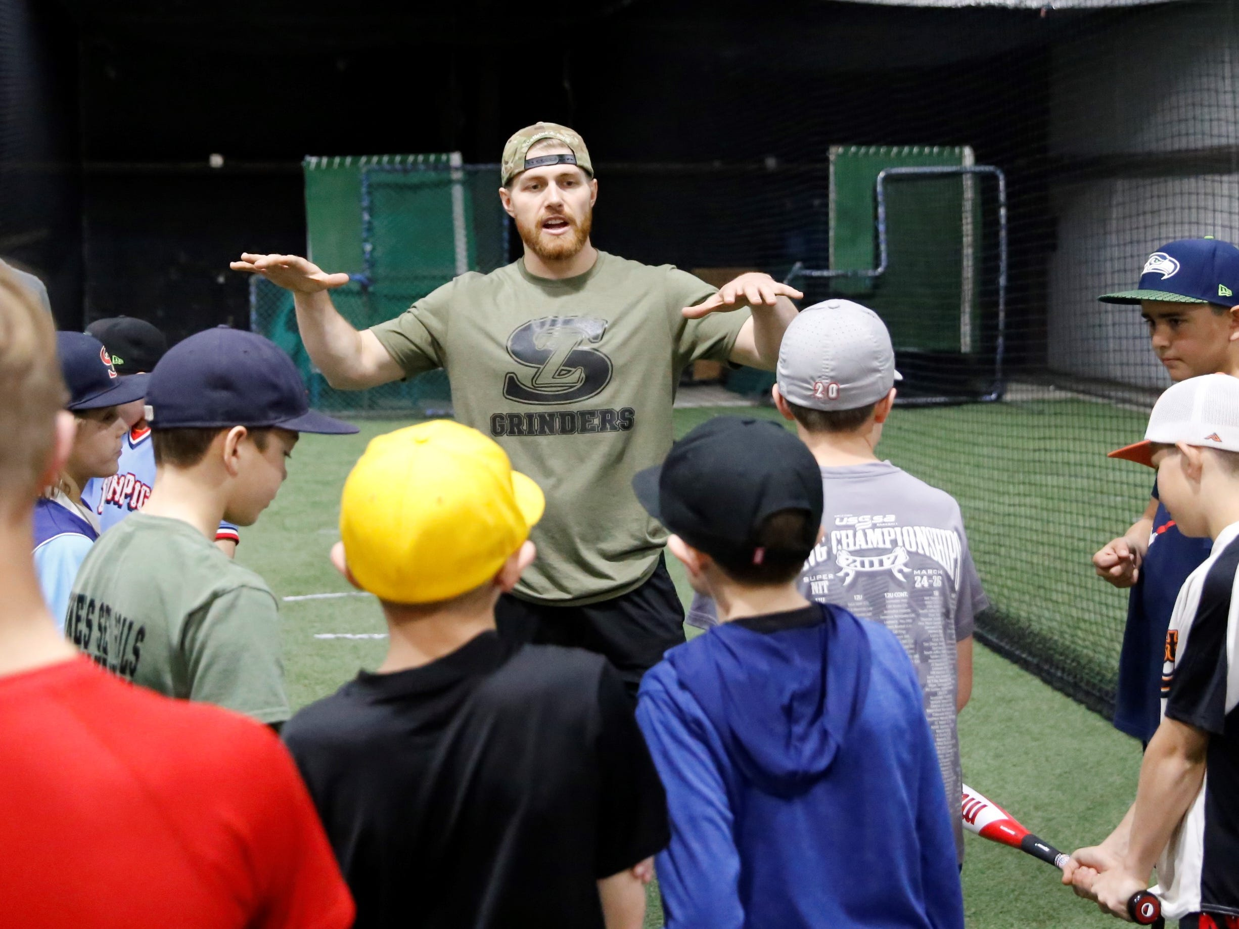 Grinders for Grace baseball camp instructor Jake McCasland gets his station ready for batting practice during the fourth annual camp Saturday at the Strike Zone training facility in Farmington.