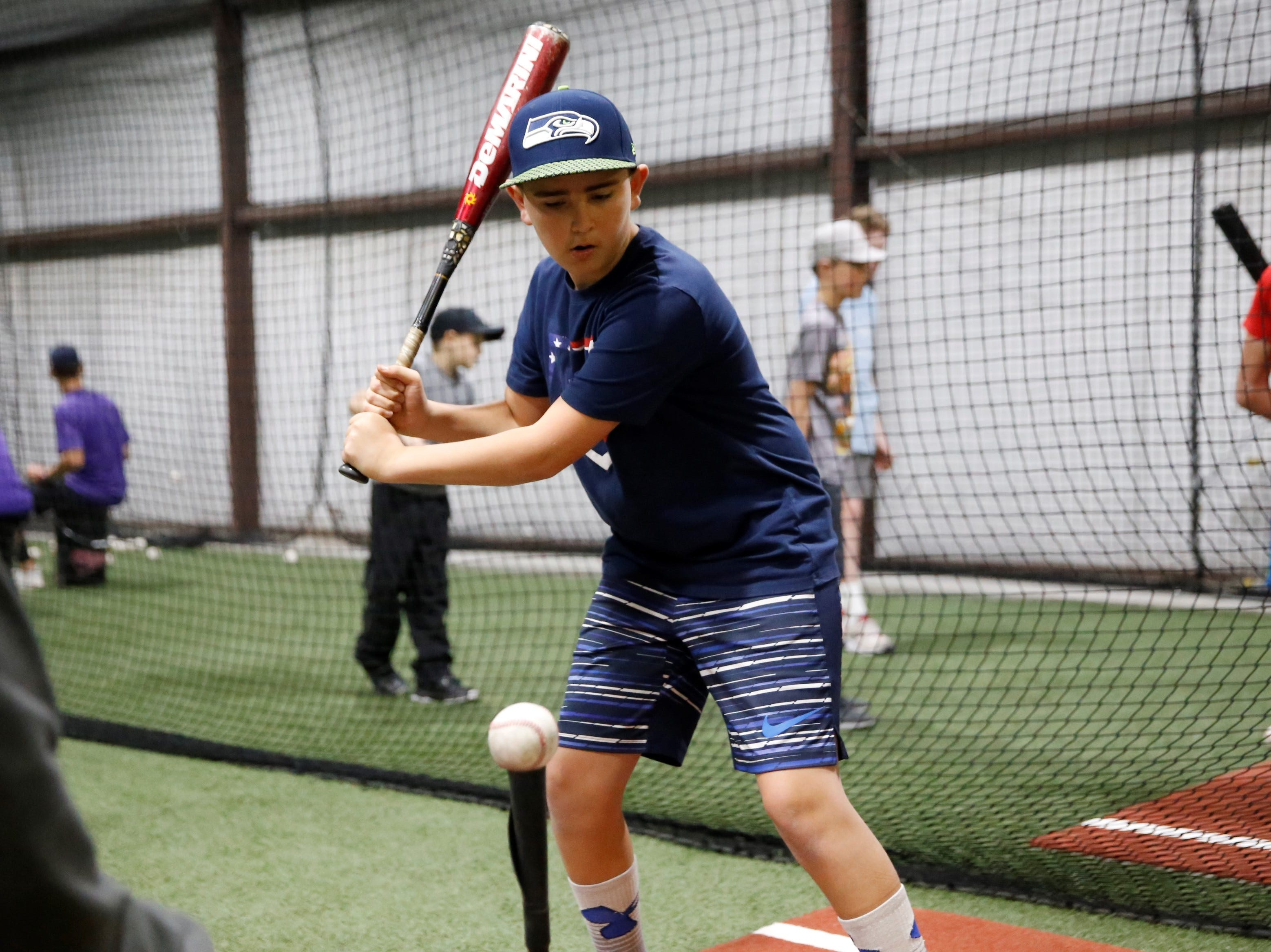 Austin Romero of Durango, Colorado, works on batting drills at the fourth annual Grinders for Grace baseball camp Saturday at the Strike Zone training facility in Farmington.