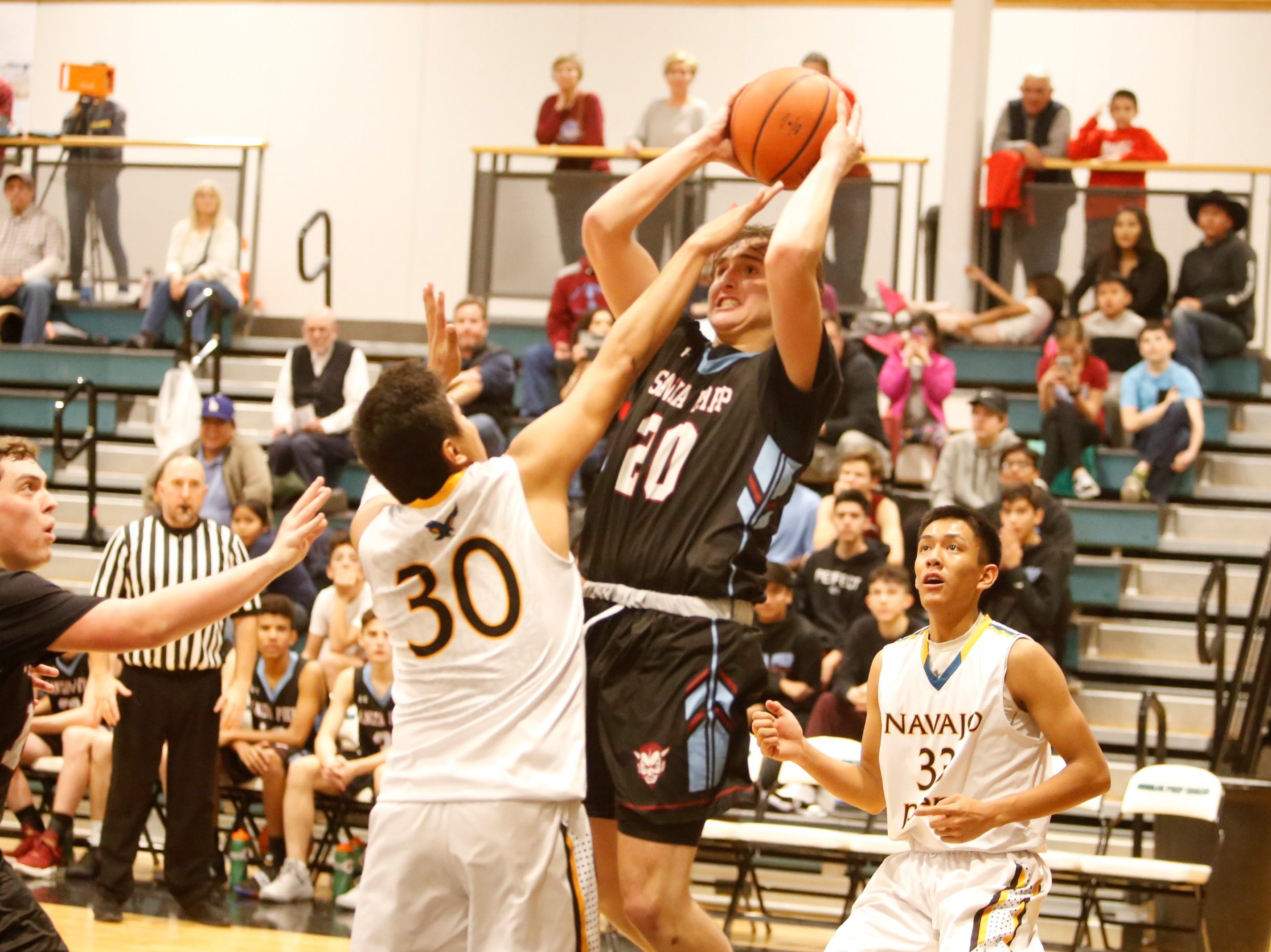 Sandia Prep's Max Feit knocks down a contested shot against Navajo Prep's Kasey James (30) during Friday's game at the Eagles Nest in Farmington.