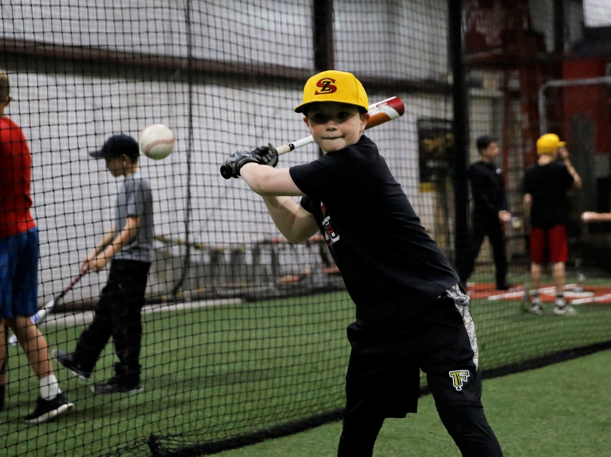 Kolby Wirth of Cortez, Colorado, swings at the ball during line-drive batting drills at the fourth annual Grinders for Grace baseball camp Saturday at the Strike Zone training facility in Farmington.