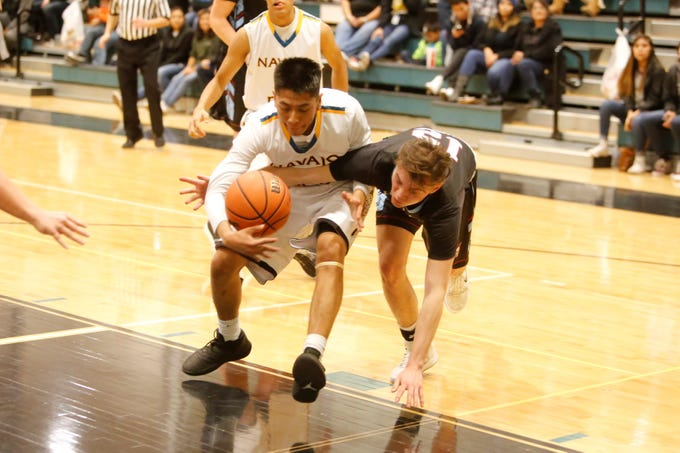 Navajo Prep's Treston Yazzie and Sandia Prep's David Gelb fight for possession of the ball during Friday's game at the Eagles Nest in Farmington.