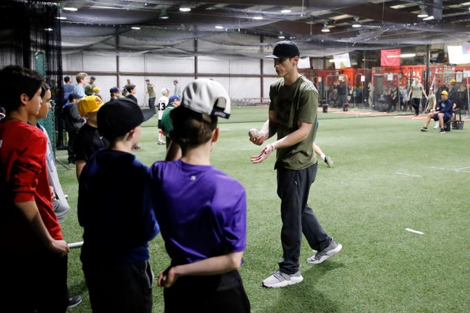 Grinders for Grace baseball camp instructor Jacy Cave, a Piedra Vista baseball graduate and former minor league player, talks to campers at his station Saturday at the Strike Zone training facility in Farmington.
