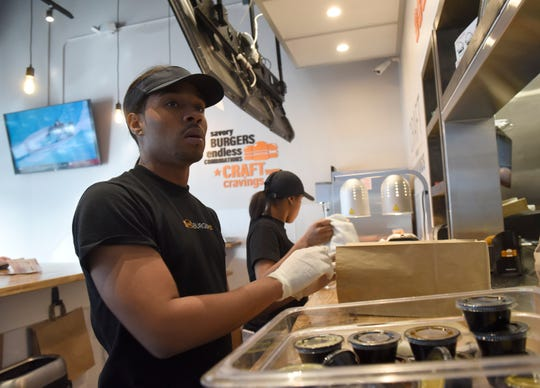 Christopher Thomas packs takeout orders at Burgerim in Bingham Farms in this file photo. The restaurant recently reopened under a new franchise owner after some water damage left the restaurant closed for months.