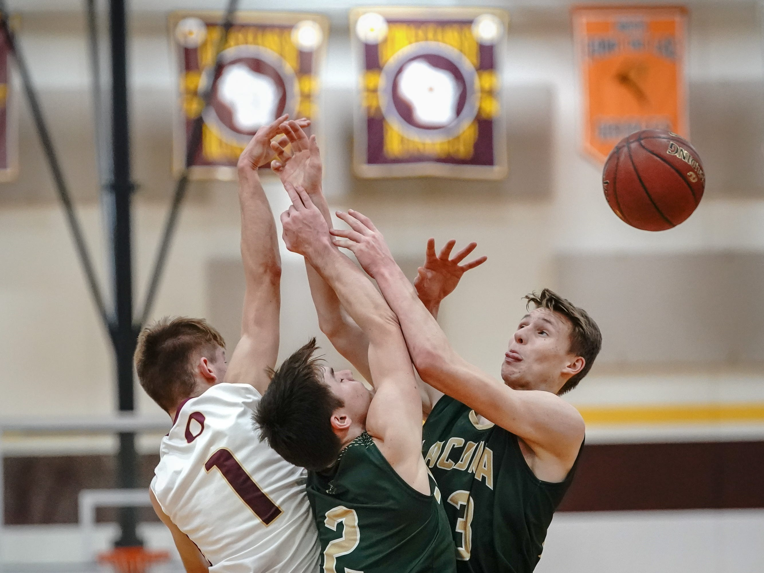 Trevor Molitor (1) of Omro and Caden Wittchow (2) and Reed Gunnink (3) of Laconia battle for a rebound. The Omro Foxes hosted the Laconia Spartans in a Flyway Conference basketball game Friday evening, January 11, 2019.