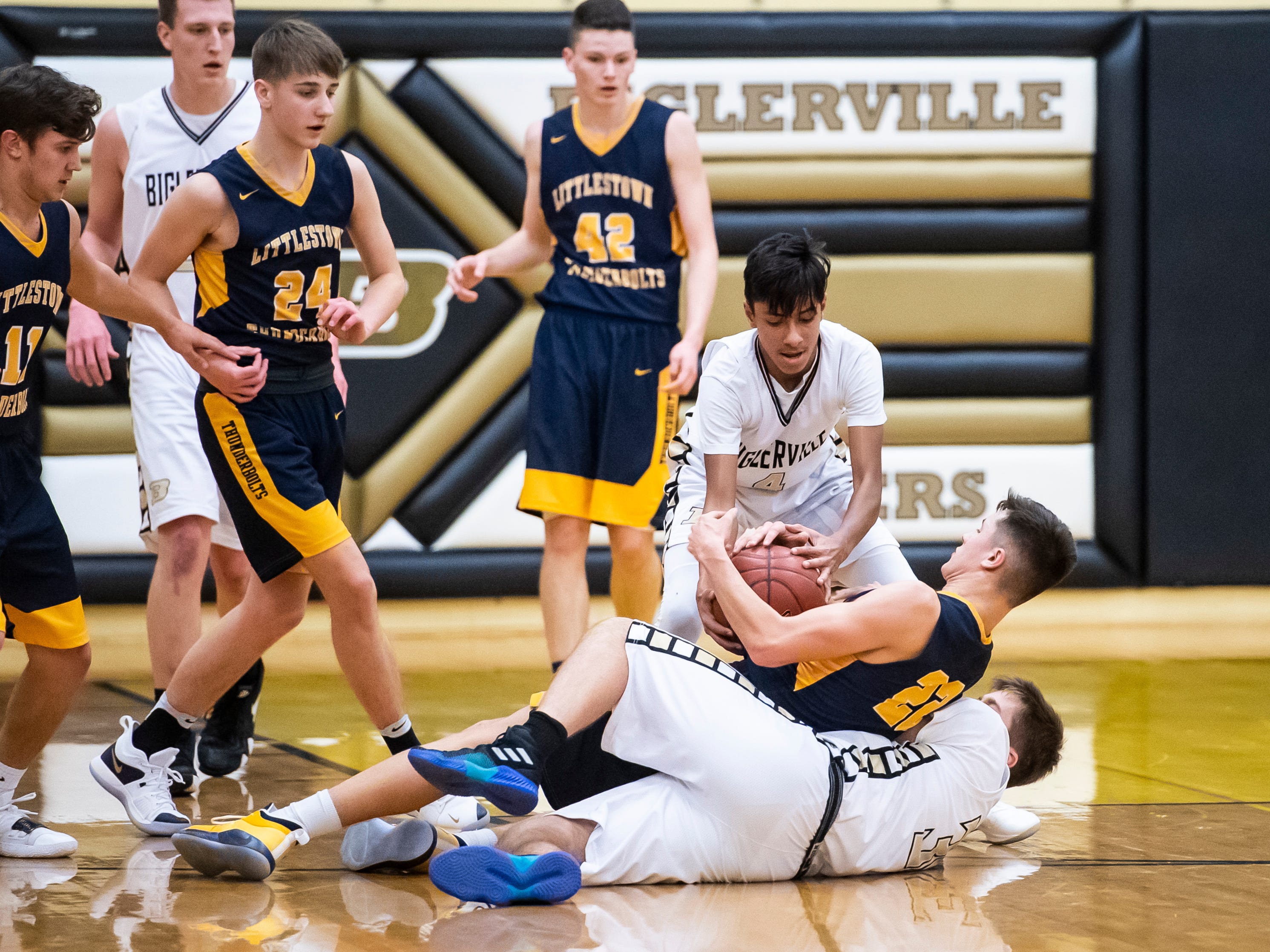 Littlestown's Logan Collins (22) maintains possession as Biglerville's Jorge Cervantes tries to take the ball on Friday, January 11, 2019. The Bolts won 65-38.