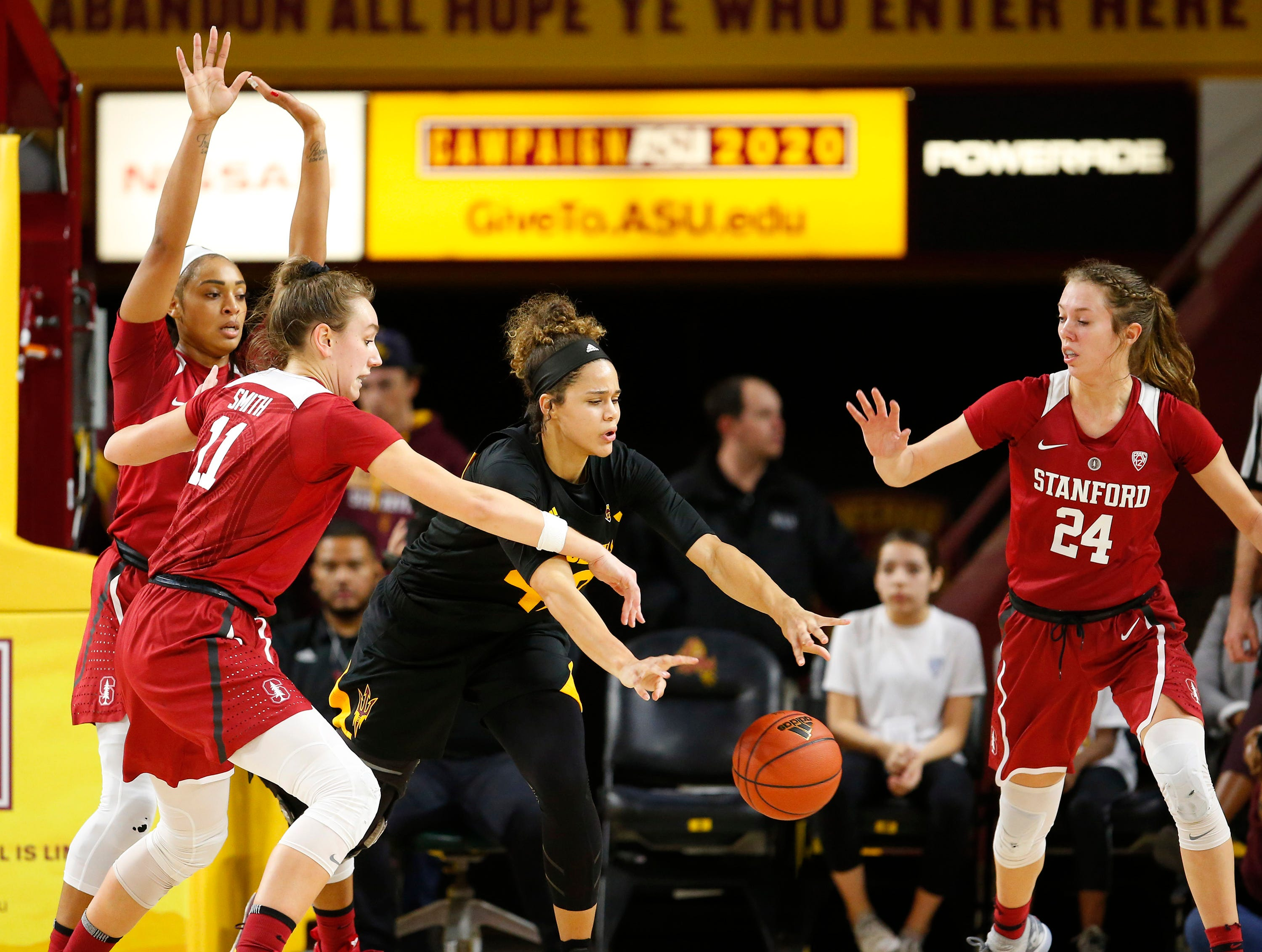 Arizona State University Kianna Ibis (42) passes the ball while being guarded by Stanford University Alanna Smith (11) and Lacie Hull (24) during a women's basketball game at Well Fargo Arena in Tempe on January 11.