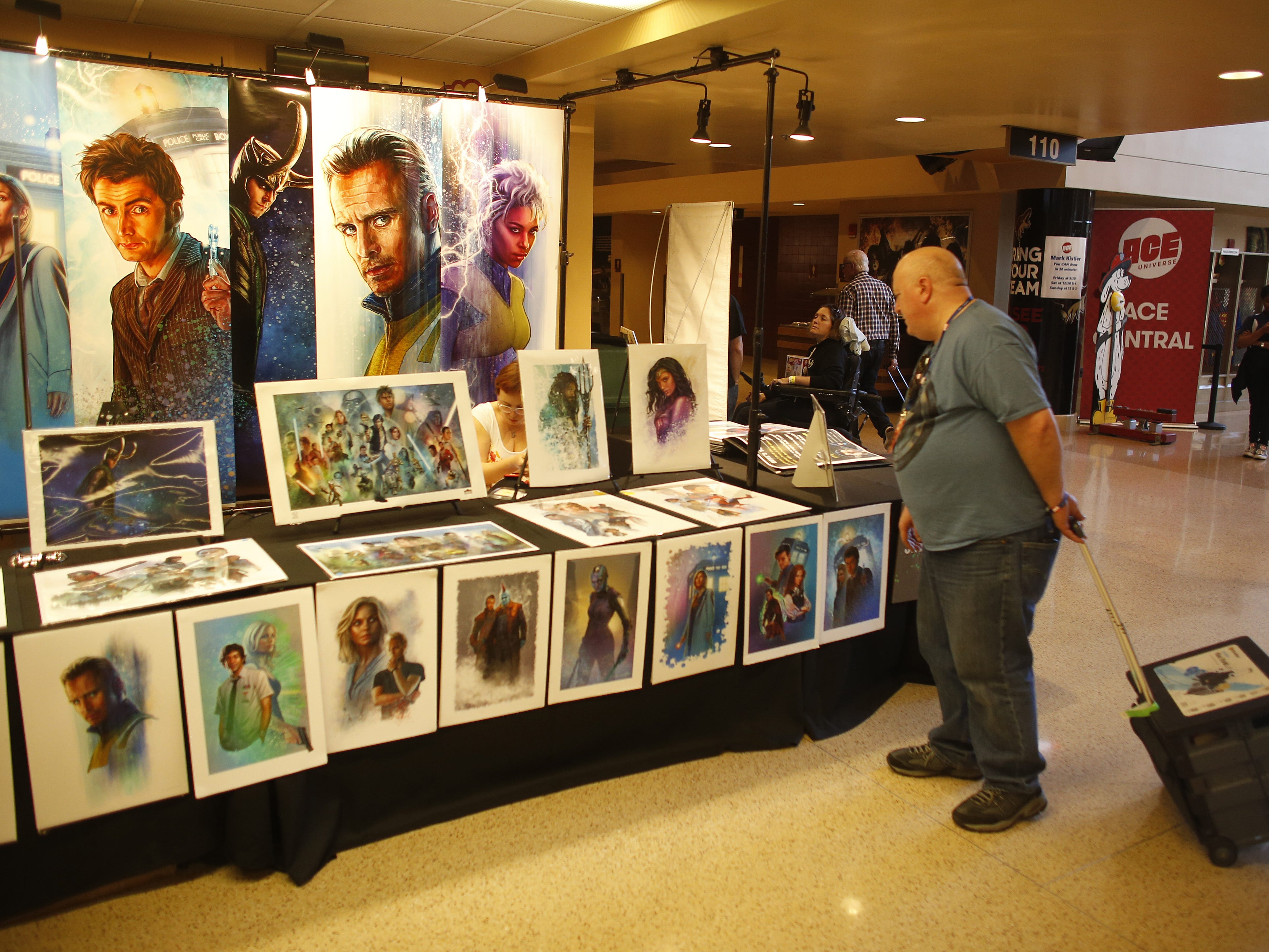 People stop and browse art from Jason Palmer on opening day of Ace Comic Con 2019 at Gila River Arena in Glendale, Ariz. on Jan. 11, 2019.