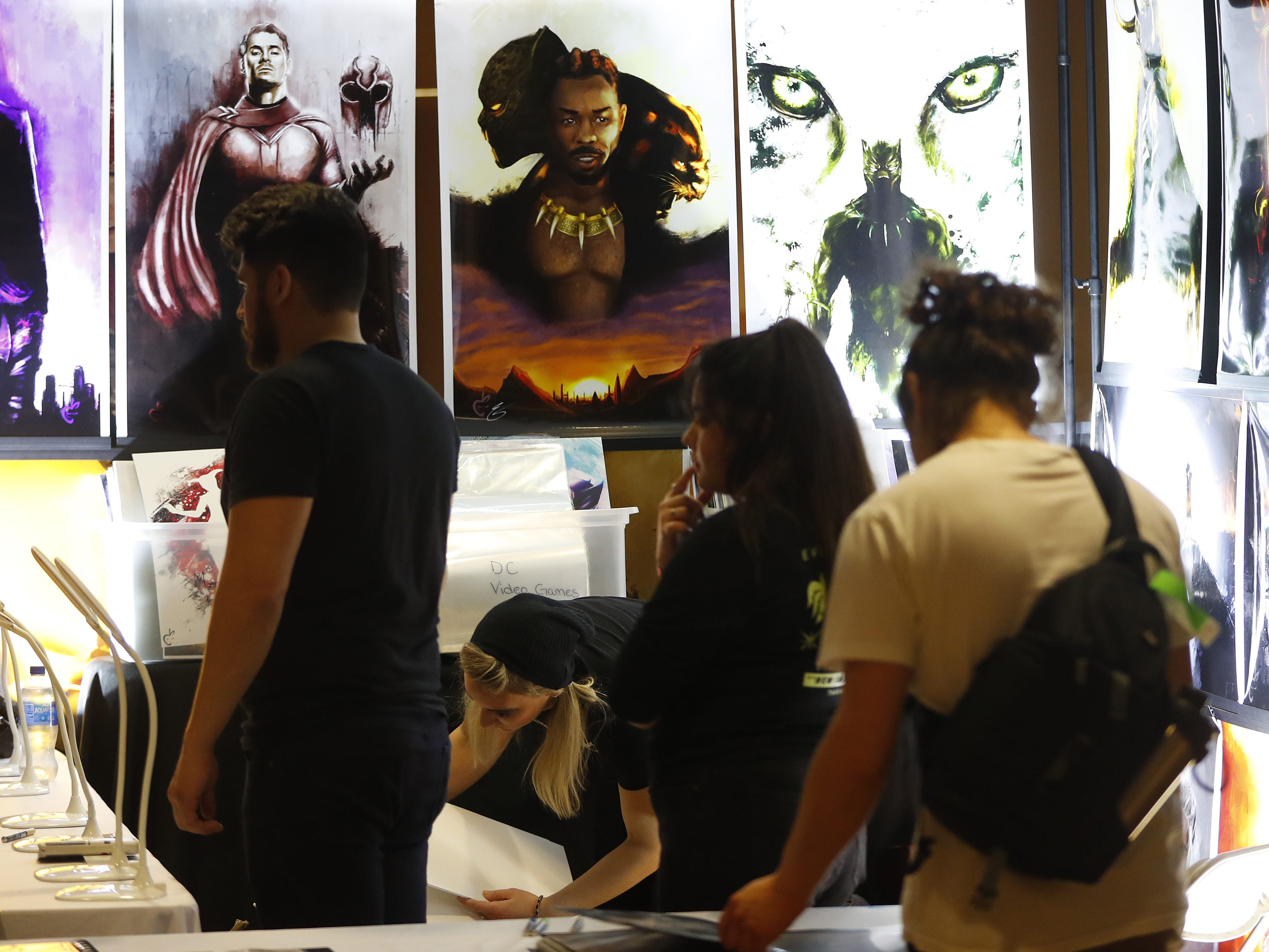 Art for sale draws onlookers during the opening day of Ace Comic Con 2019 at Gila River Arena in Glendale, Ariz. on Jan. 11, 2019.
