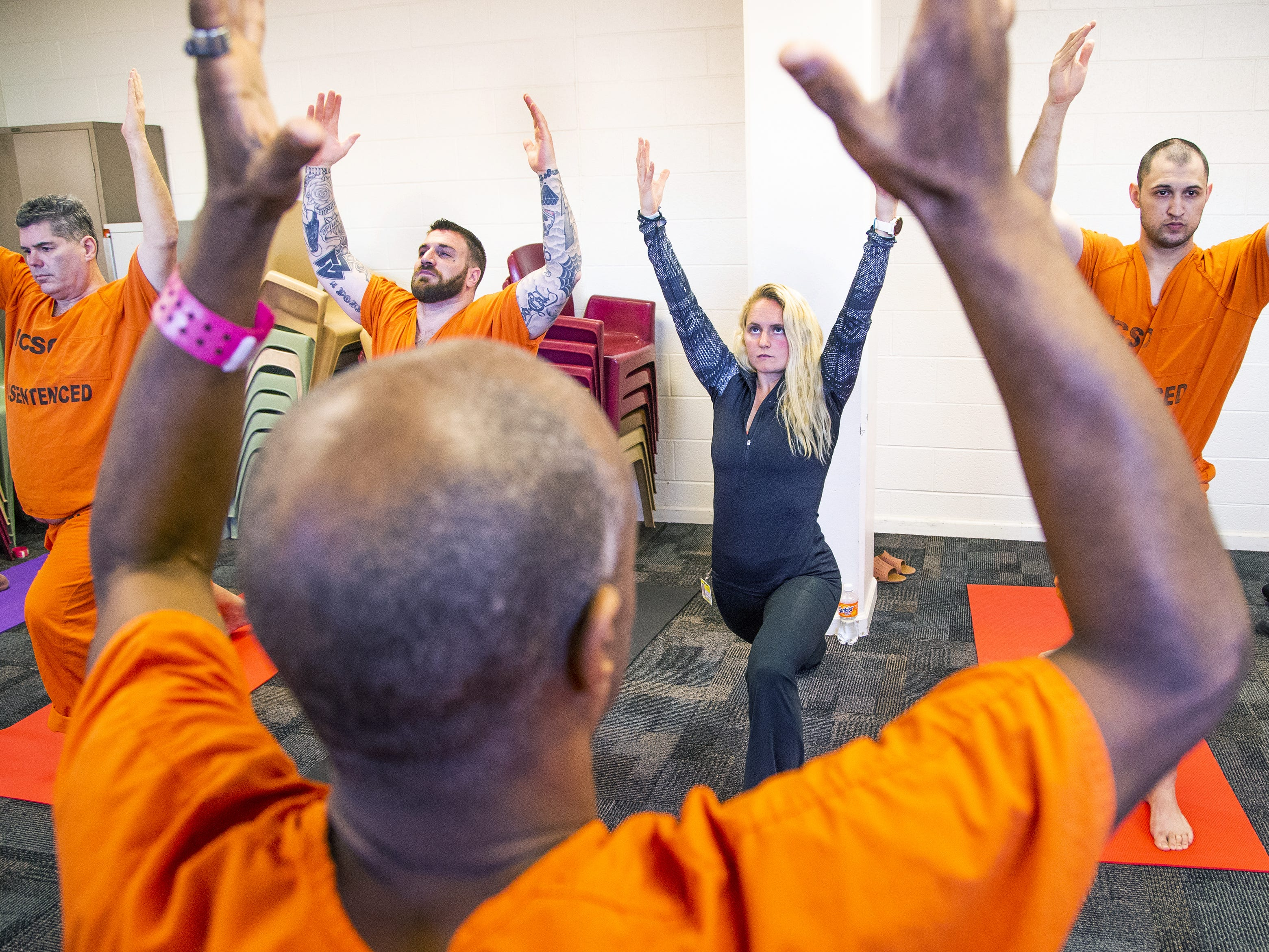 Volunteer Allison Merlo helps run a yoga class offered by the Prison Yoga Project Phoenix at the Maricopa County Towers Jail complex on Jan. 11, 2019.