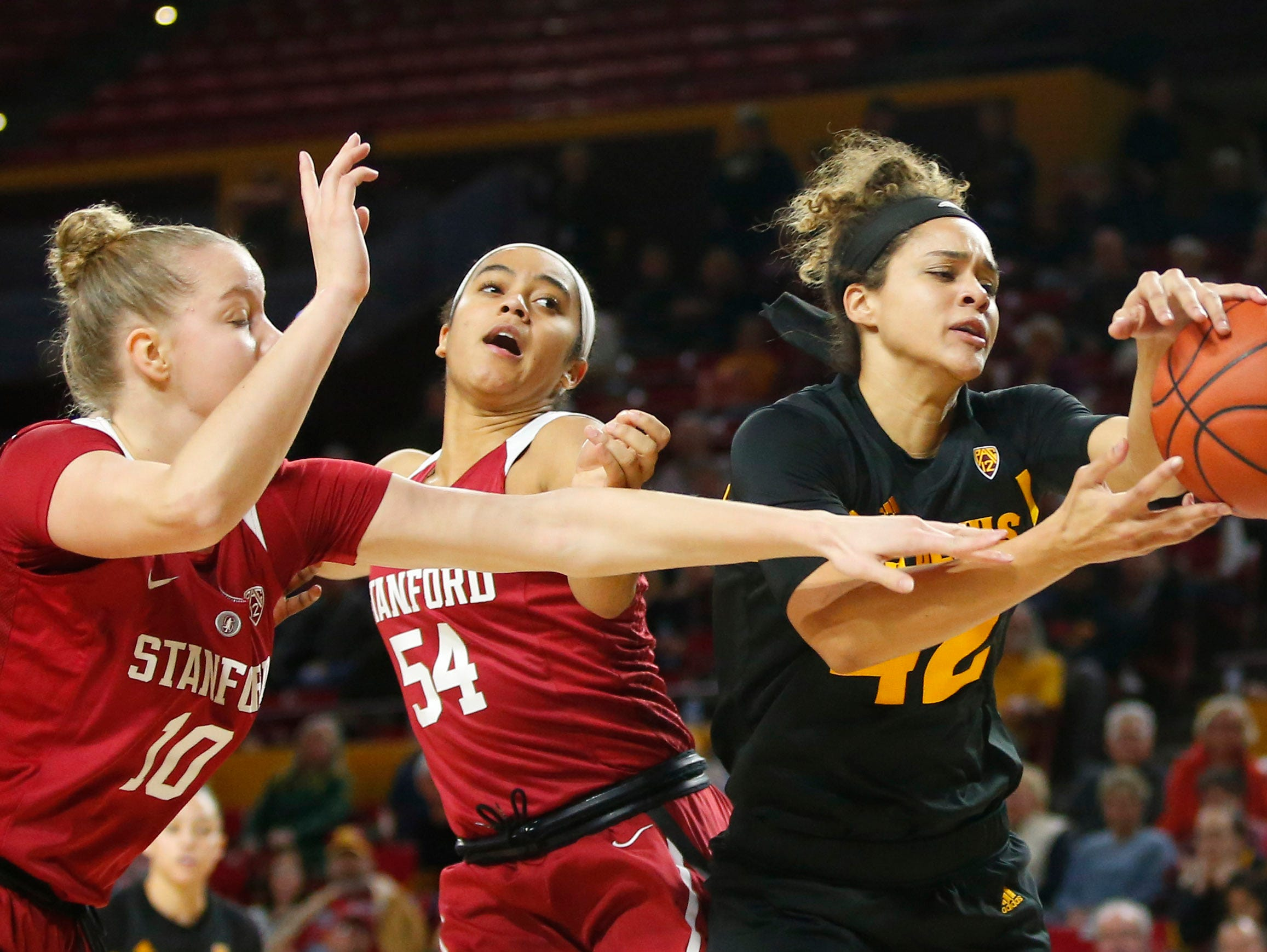 Stanford University Alyssa Jerome (10) and Jenna Brown (54) battle Arizona State University Kianna Ibis (42)  for the rebound during a women's basketball game at Well Fargo Arena in Tempe on January 11.