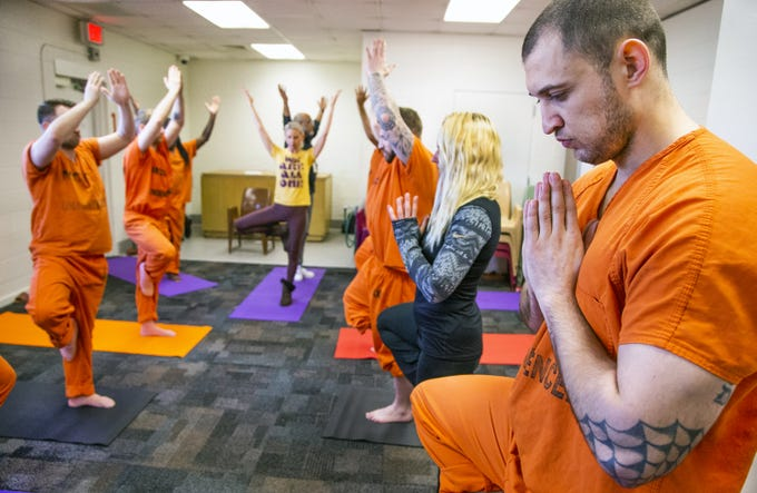 Inmate Erik VanVoorhis (right) and volunteer Allison Merlo (second from left) practice yoga during a class offered by the Prison Yoga Project Phoenix at the Maricopa County Towers Jail complex on Jan. 11, 2019.
