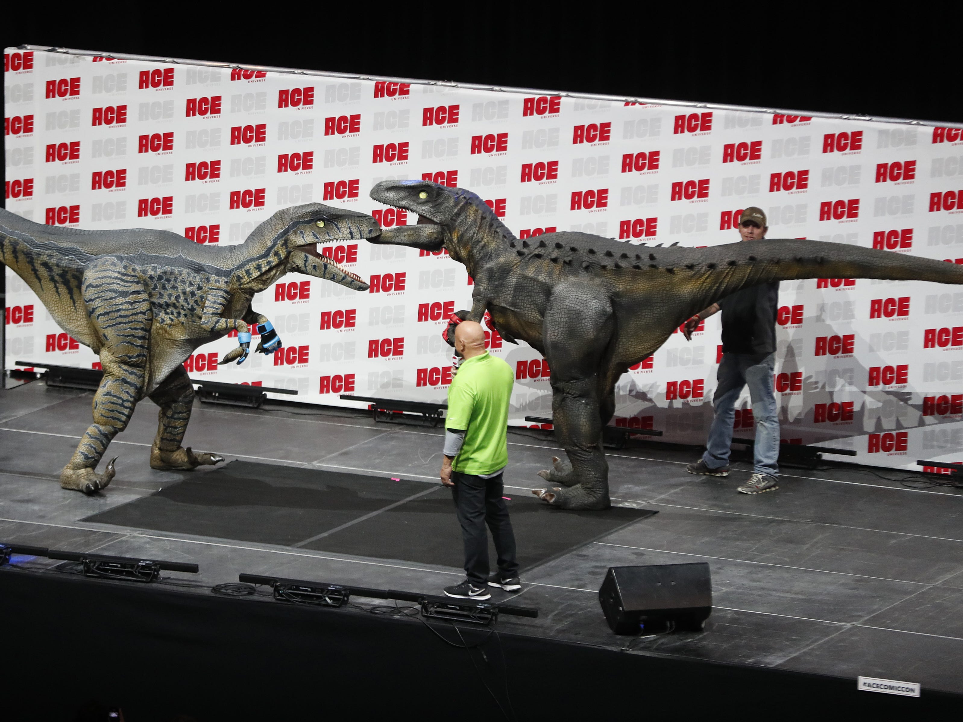 Two dinosaurs take the main stage for a mock fight promoting Jurassic Fight Night in February during the opening day of Ace Comic Con 2019 at Gila River Arena in Glendale, Ariz. on Jan. 11, 2019.