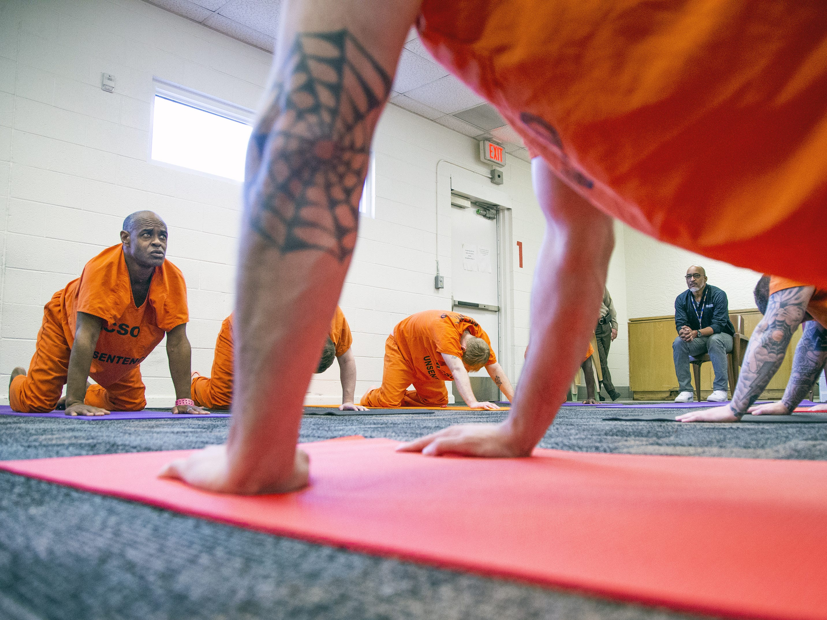 Dr. Julian Wyatt (at right in black shirt),  the director of the Prison Yoga Project Phoenix, conducts a yoga class at the Maricopa County Towers Jail complex on Jan. 11, 2019.