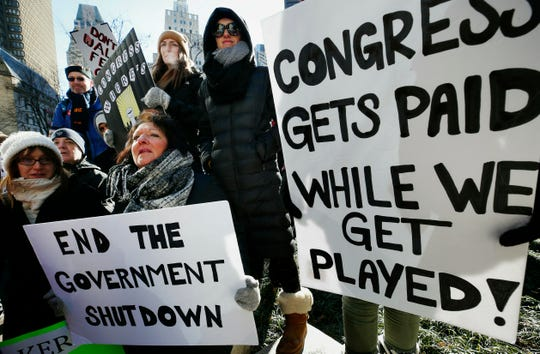 Government workers and their supporters hold signs during a protest in Boston, Friday, Jan.11, 2019.