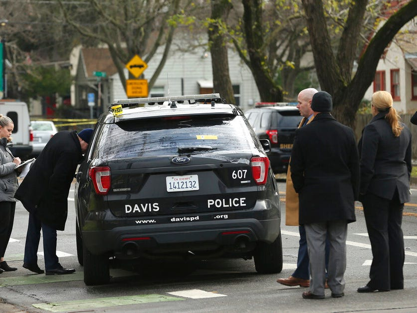 Authorities inspect the patrol vehicle driven by Davis Police officer Natalie Corona, Friday, Jan. 11, 2019, in Davis, Calif. Corona, 22, who had been on the job only a few weeks, was shot and killed Thursday. The suspect was later found dead from a self-inflicted gunshot.