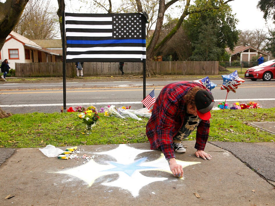 Matthew Ottele draws a star on the sidewalk Friday, Jan. 11, 2019, near the scene were Davis Police Officer Natalie Corona was shot and killed in Davis, Calif. Corona, 22, who had been on the job only a few weeks was slain, Thursday, by a suspect who opened fire as she was investigating a three-car crash. The suspect was later found dead from a self-inflicted gunshot, following a standoff with officers.