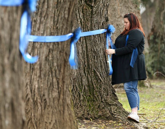 Vicky Oliverius ties blue ribbons on trees, Friday, Jan. 11, 2019, near the scene were Davis Police Officer Natalie Corona was shot and killed in Davis, Calif. Corona, 22, who had been on the job only a few weeks was slain, Thursday, by a suspect who opened fire as she was investigating a three-car crash. The suspect was later found dead from a self-inflicted gunshot, following a standoff with officers.